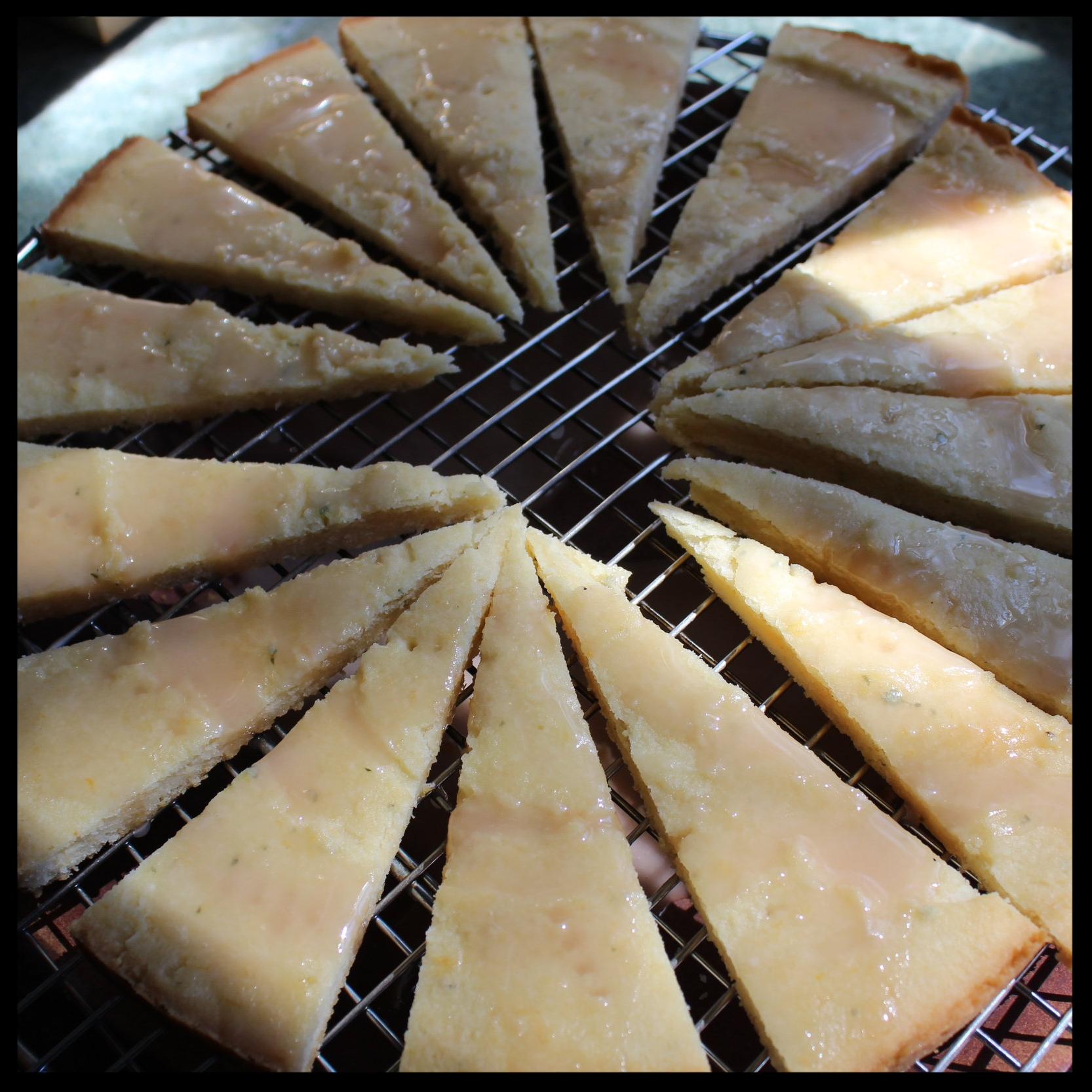 11. Remove the collar from the pan. Immediately cut the shortbread into 8 or 16 wedges.  12. Transfer wedges to a cooling rack set over a plate.  13. Drizzle the glaze evenly over the shortbread, and gently spread to the edges with an offset spatula. Once cool you can serve it!