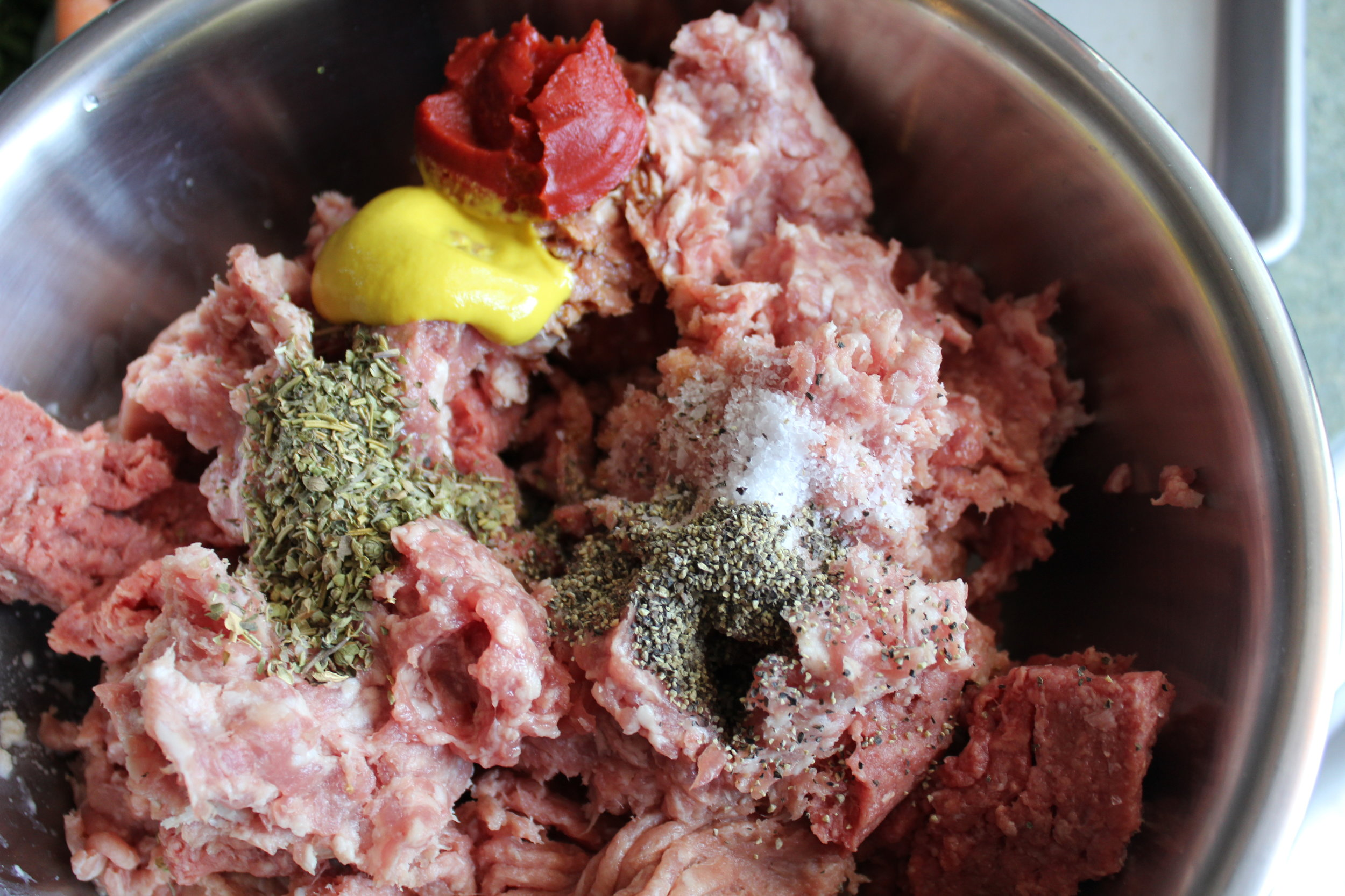 3.  Add the beef, turkey and pork. Sprinkle with the Italian seasoning, Worcestershire sauce, salt, pepper, 1 TB of the tomato paste and mustard and mix until blended. Using your (clean) hands here is perfectly fine.