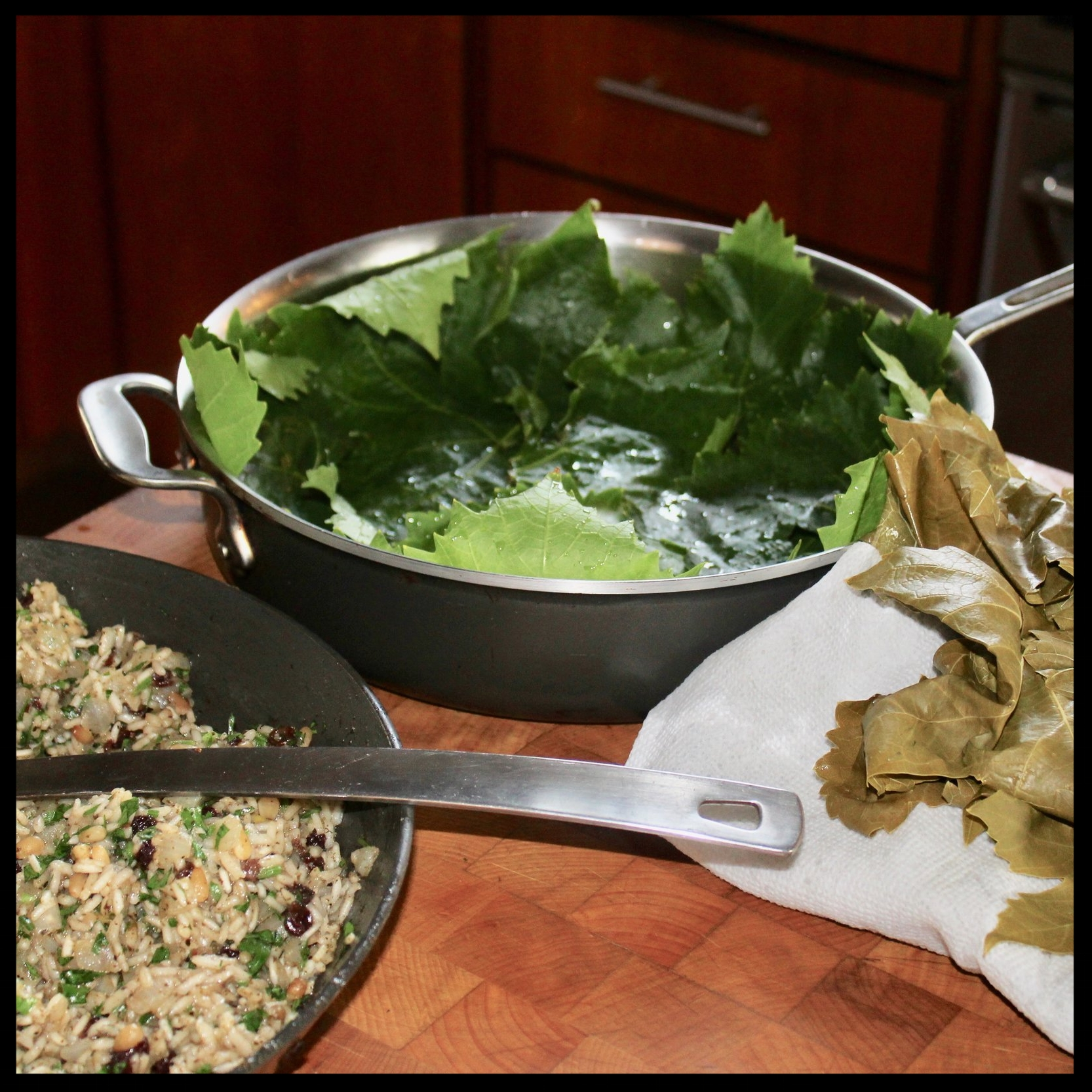 6. Line a straight-sided large pan with about 10-12 grape leaves (use the torn or imperfect ones here).  7. Line up your leaves, your pan and your filling in one place.  8. Grab a tablespoon. Let's fill these babies!