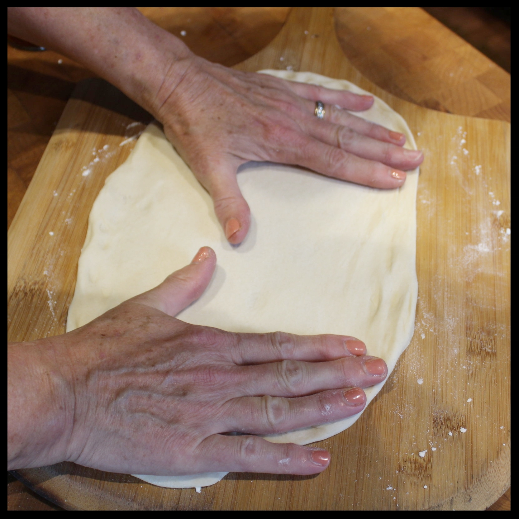 9. Flour your surface and now with palms flat, urge the dough out by moving your hands apart. Rotate the dough and do this again until you have a nice round.