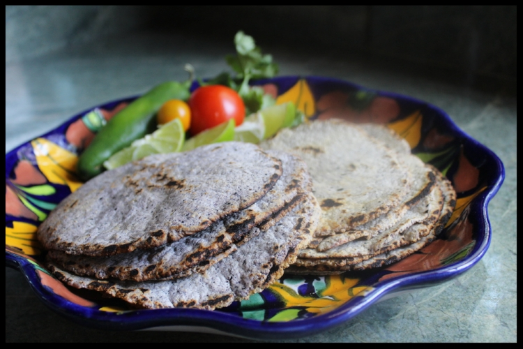 CORN TORTILLAS are really easy to make, they are naturally gluten free, and unlike flour tortillas, require no addition of fat or lard.  Lime is added to all masa (corn flour) to alkalinize it, add flavor, and coincidentally, adds calcium as well.  Corn tortillas are loaded with fiber and anti-oxidant rich anthocyanins. BONUS!  I used blue corn masa for this recipe and tried it two ways - on the left I used 100% blue masa, and on the right 1/2 blue and 1/2 regular corn.  The color difference is apparent, but quite honestly, the flavor wasn't.  Since blue corn masa tends to cost a bit more, making them 1/2 and 1/2 saves a little dough (pardon the pun)!  All you'll need to make these is a bowl and a heavy bottom or cast iron griddle/pot/pan.  I used a little cast iron round griddle that I had hanging around.  The secret to cooking these is to get that pan or griddle blazing hot so you can cook the tortillas and get that tasty char on the edges.  If you don't have a tortilla press, you can spray 2 sheets of wax paper, put your dough ball in between, and then use a rolling pin to make your tortilla.  Alternately, you can take a heavy, flat pot, and use it to press the dough ball between the 2 sheets of wax paper.  Any or all will work.  This is a great project to work on with your kids or grandkids.  I like them freshly cooked with a little butter, a squeeze of lime and a dash of salt. Delicioso! This recipe will make approximately 10 tortillas.