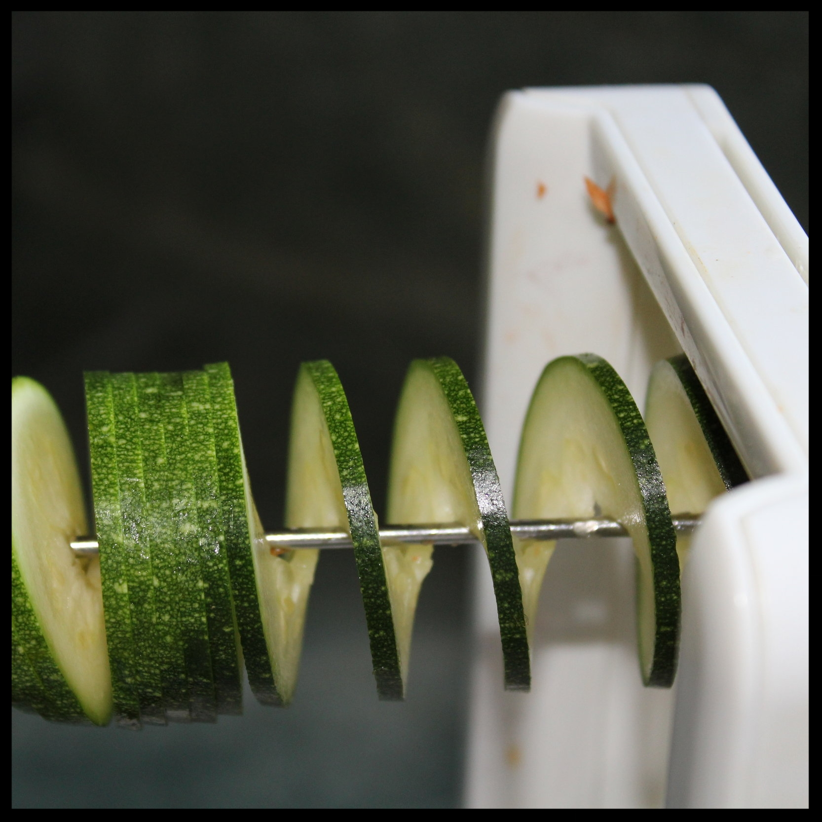 Now, run the skewer through hole in the blade plate and back into the vegetable (see the photo on the left). After several turns you'll see that the vegetable remains in one piece, but becomes a continuous corkscrew, almost like a Hawaiian lei.