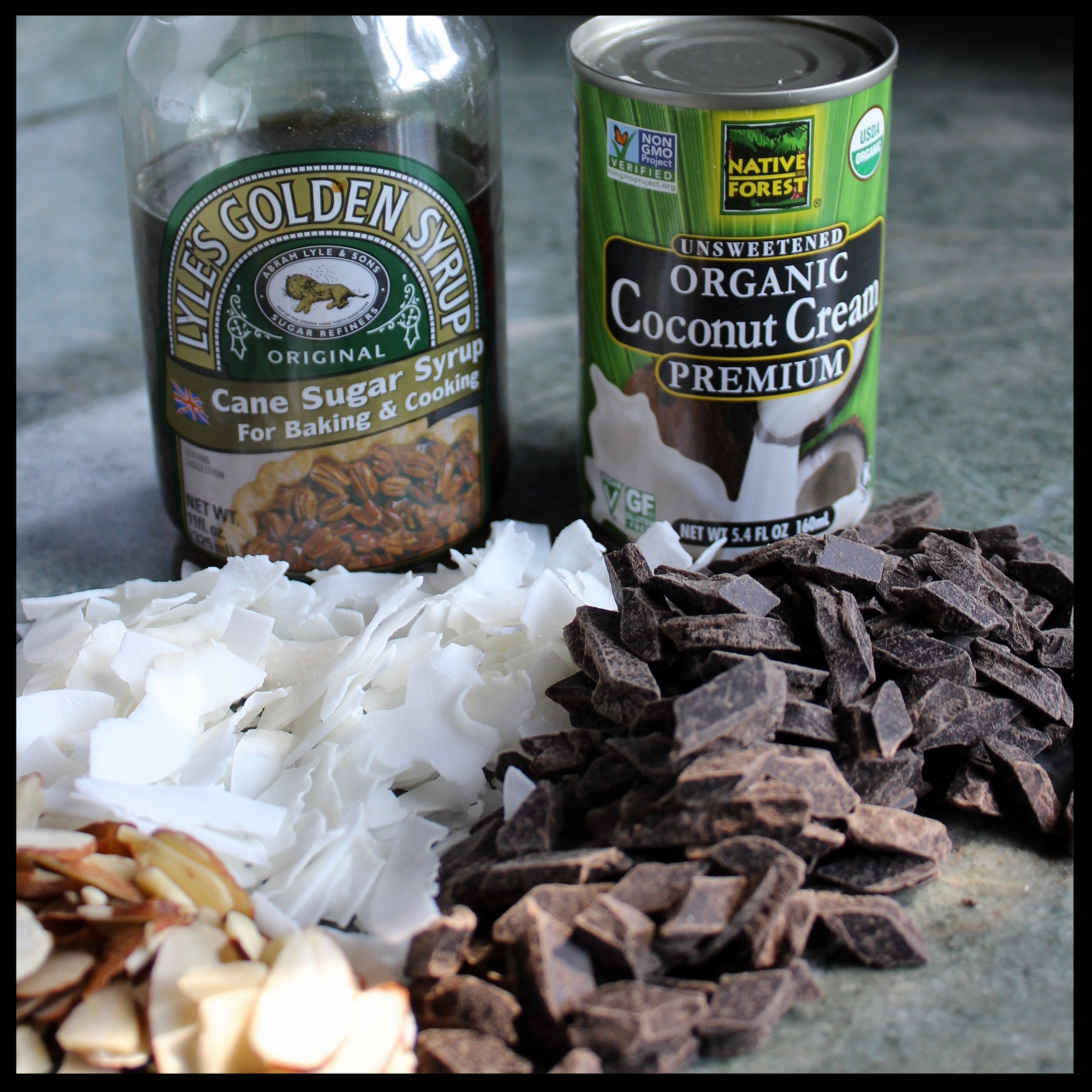 INGREDIENTS:   -  12 ounce bag of semi-sweet dark chocolate  -  3 cups unsweetened untoasted coconut  -  1/2 tsp salt  -  4 TB (2oz)   Lyles Golden Syrup  (or light corn, maple or date syrup)  -  6 TB Coconut Cream   -  1 tsp vanilla extract  -  1 TB key lime or lime zest (optional)  -  Slivered toasted almonds for garnish