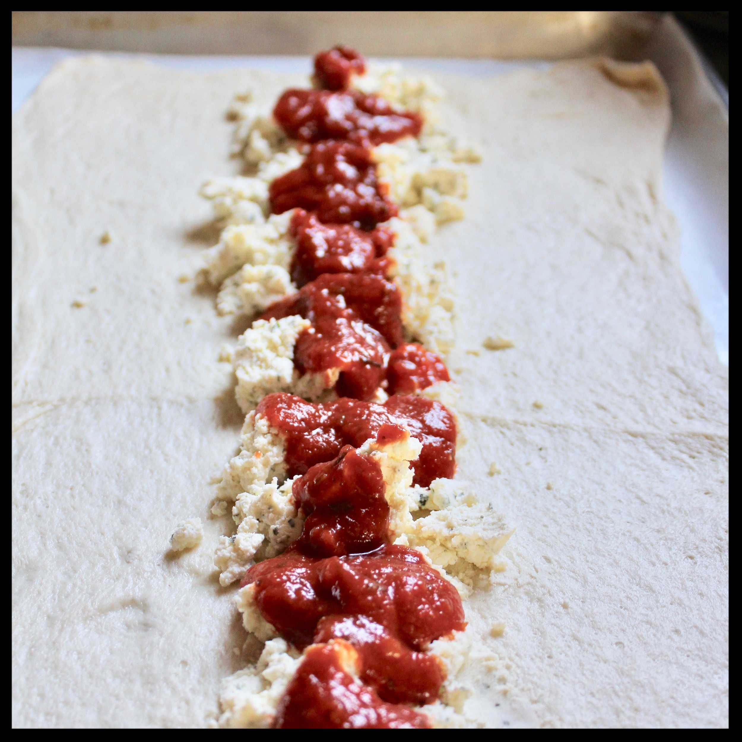 3.  Next add your favorite prepared marinara - roughly 1/2 cup spooned evenly over the cheese.
