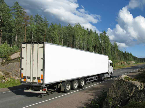 """White """"big-rig"""" truck on two-lane rural highway with trees in the background."""