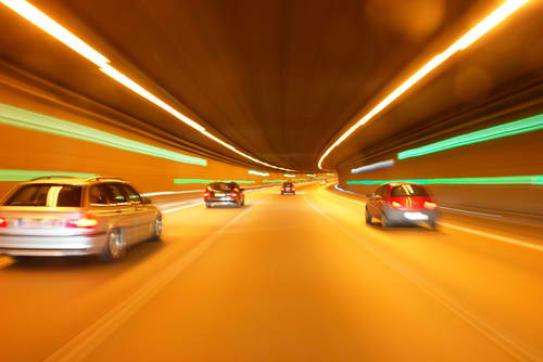 Time-lapse photo of cars going through an underground tunnel.