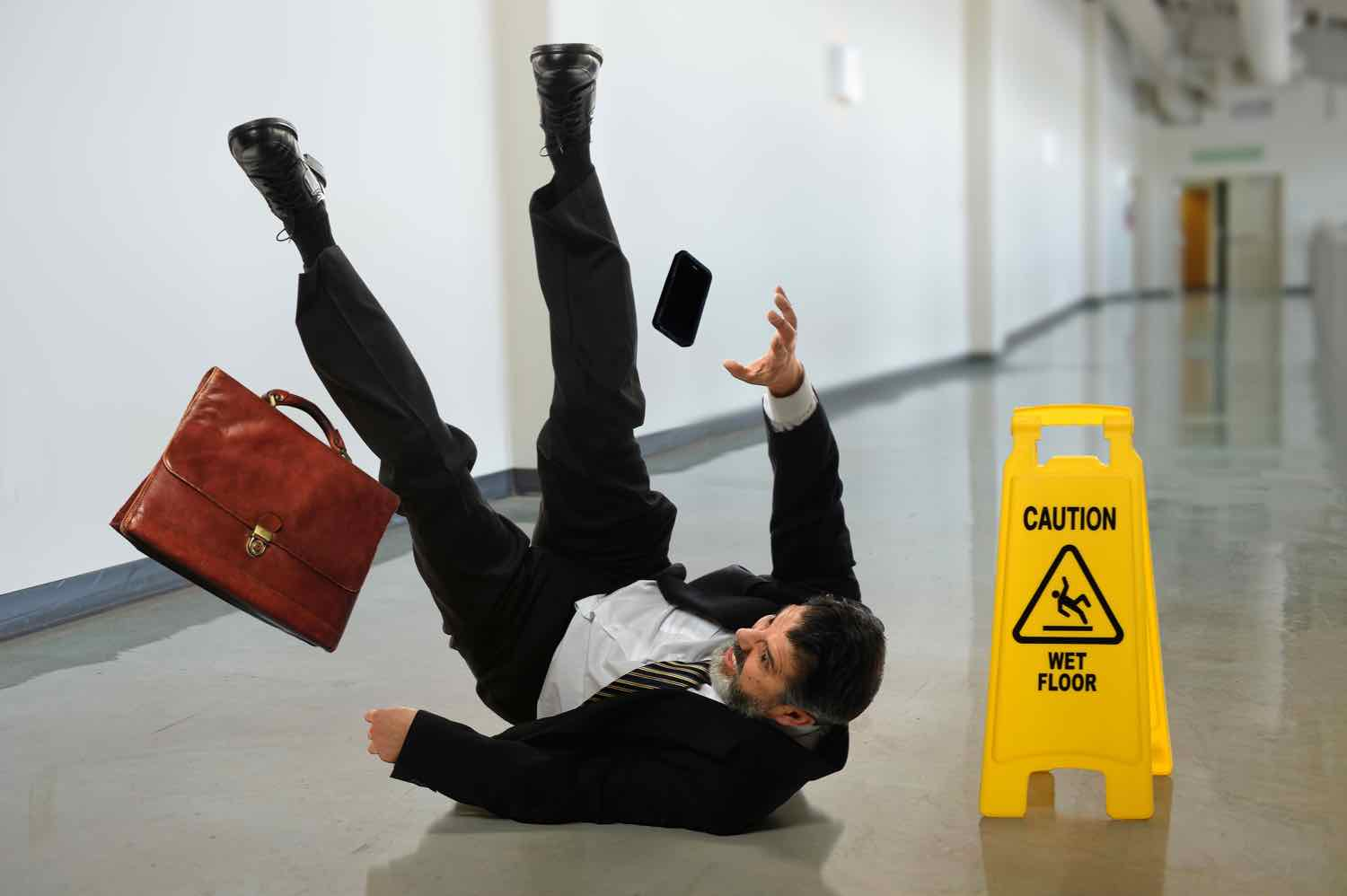 Businessman slipping and falling on a slippery/wet floor in an office building.
