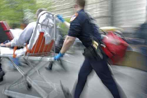 Blurry photo of a paramedic wheeling out a patient.
