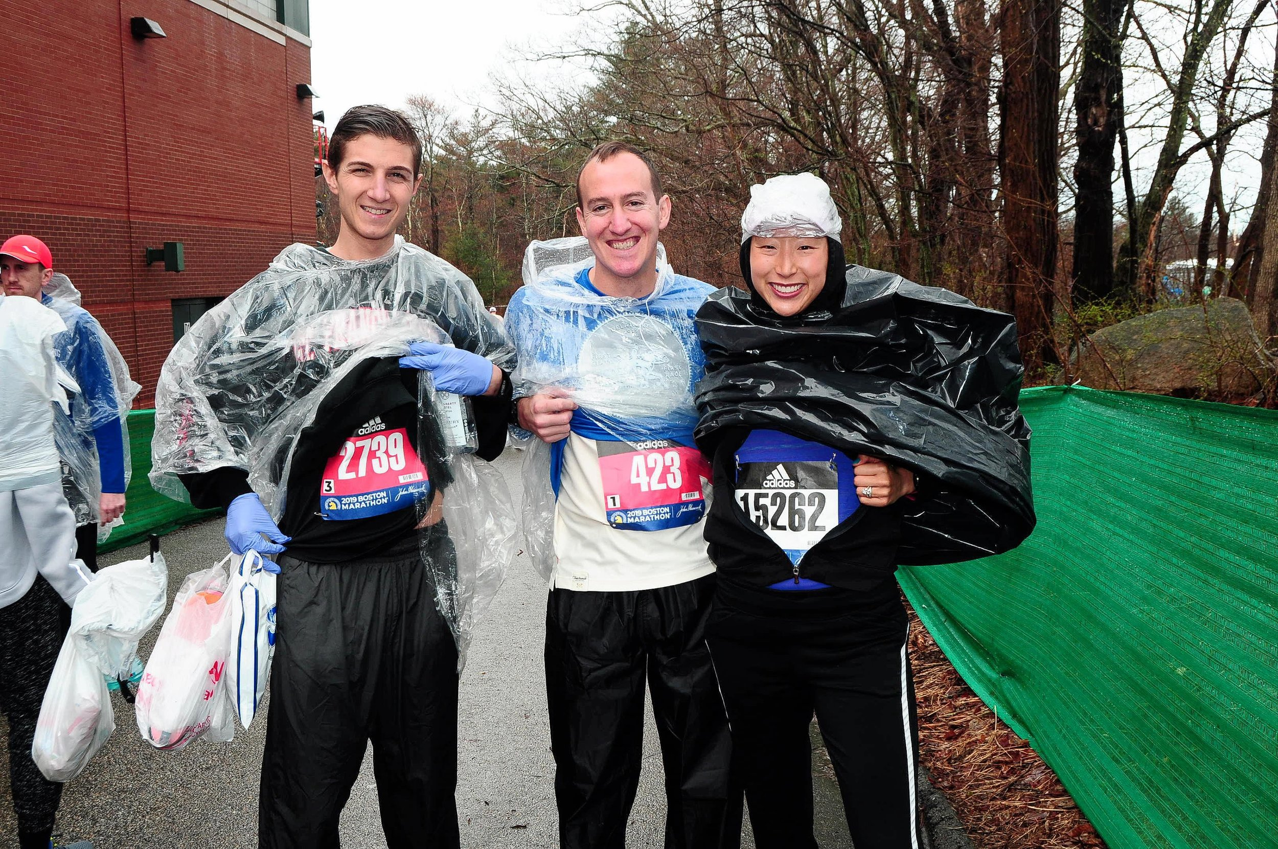 Justin Perkins, Brent Frissora and Eva Frissora on Marathon Monday morning, ready for the rain