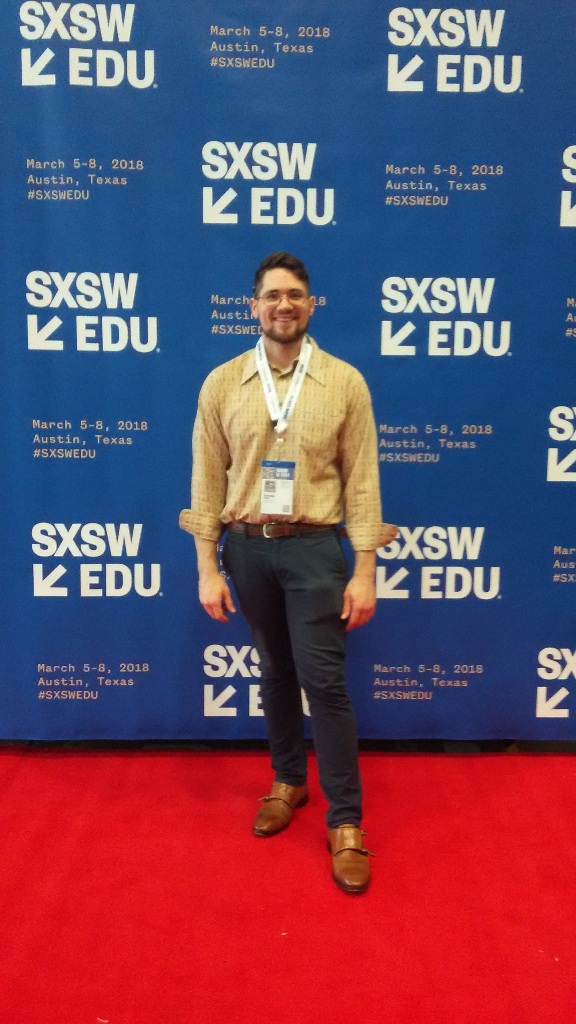 Donnie Welch a young white male with brown hair, a beard, and glasses stands on a red carpet with a blue banner for SXSWedu 2018 behind him. The blue banner his SXSWedu 2018 and the event details in white-yellow hued text. Welch is wearing tan dress shoes, blue pants and a paisley shirt.