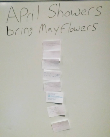 """April Showers / bring Mayflowers"" is written in black lettering on a white board. Below that in a vertical column are note cards. It's clear that there's writing on the cards, but the writing itself is illegible in the photo."