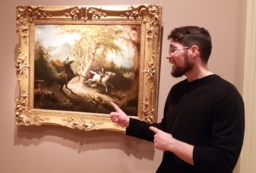 "Donnie Welch, a young, white male bearded, with glasses and in a black long sleeve shirt stands in front of ""The Headless Horseman Pursuing Ichabod Crane"" (1858 oil on canvas) by John Quidor pointing at the art. The painting is a water color showing two horsemen, one the black, spectral, headless horseman on a black horse, reared up, the other a regular man on a white horse trying to ride away. The painting fairly small and in an ornate gold colored frame."
