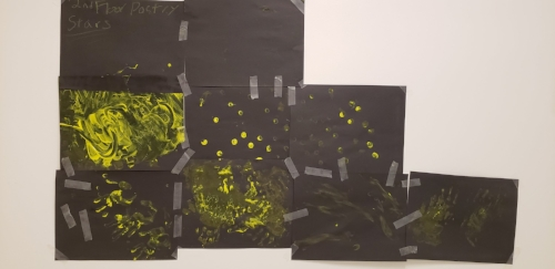 Picture of stars & constellations from a poetry workshop. Black construction paper taped together with yellow finger paint on them. To the left are two columns of three, then a column of two, then one all the way on the right. The finger painting is different in each, some dots, some swirls and some full hand prints are visible.
