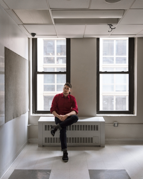 (Photo by  Julianne Nash ) Donnie Welch, young caucasian male, sits on radiator by the window of a empty classroom. He's in a red shirt, jeans, and sneakers, sitting with one leg crossed. The gray and white tile floor and white board of the classroom are visible in the foreground.