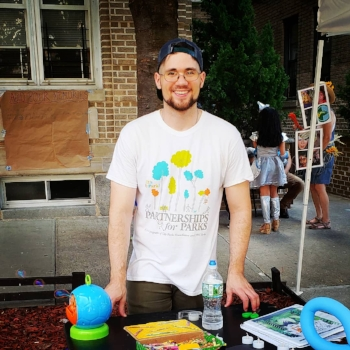 Donnie Welch, young caucasian male stands behind a table in a white T-shirt. On the table are a bubble machine, story book, and supplies for children's crafts. In the background can be seen apartment buildings and people in costume for  Wizard of Oz  party theme.
