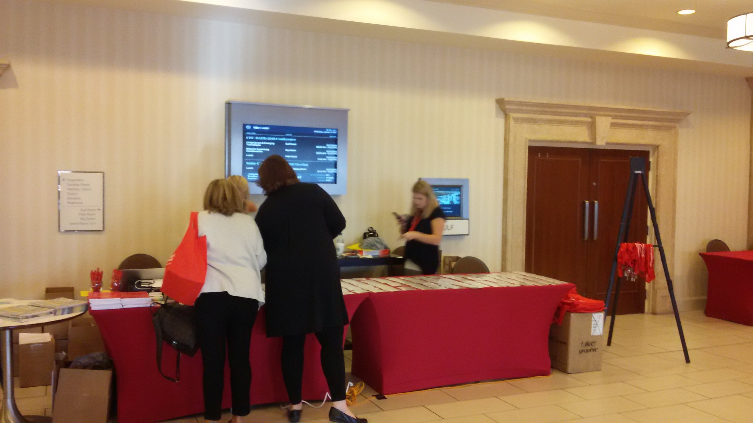 Table at the CEC-DADD 2018 conference. Two older Caucasian women look at pamphlets on a red clothed table. A Third middle-aged Caucasian women is seen checking her phone behind the table.