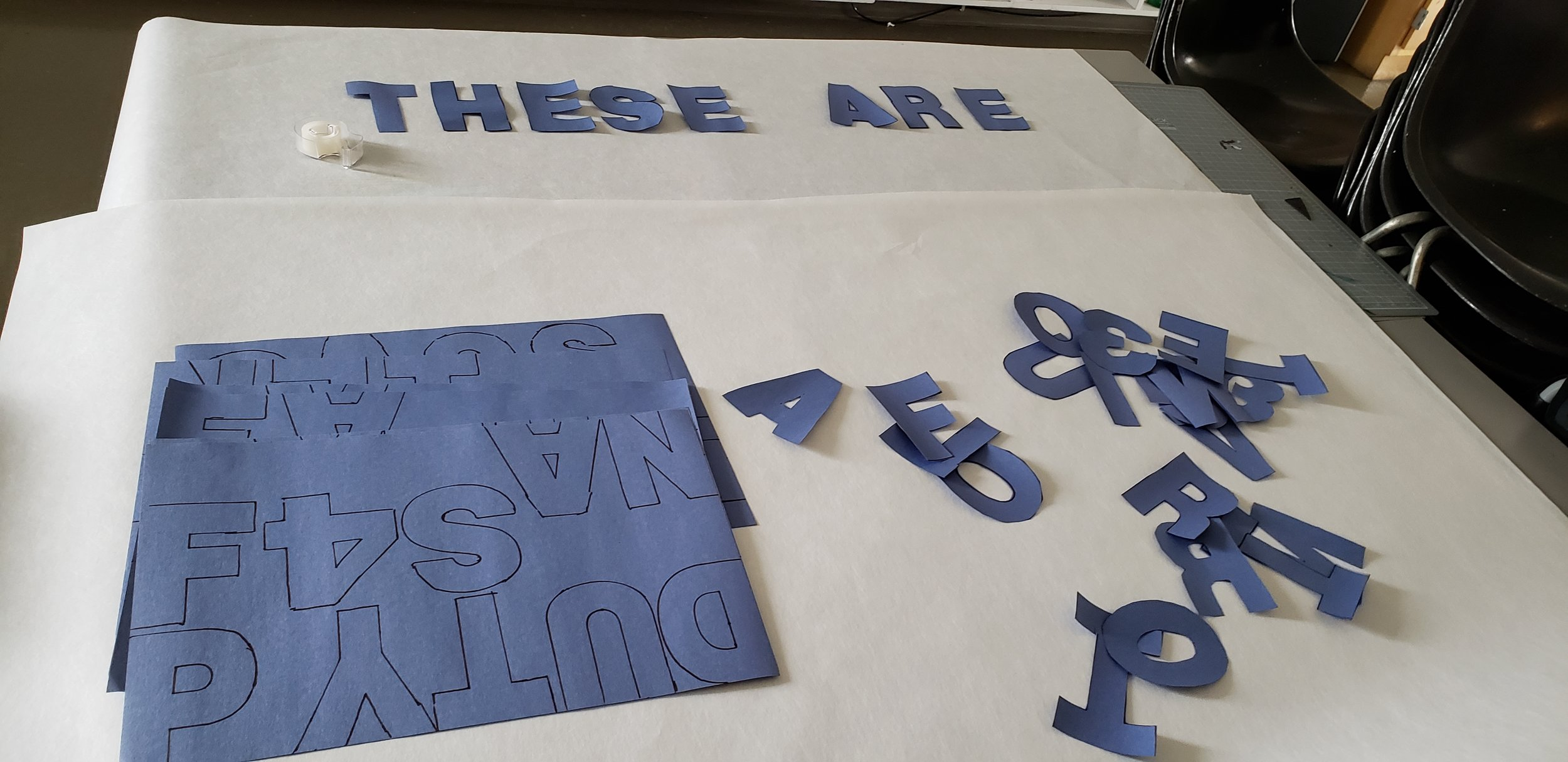 "Large white mural paper. ""These Are'"" spelled out at the top in blue letters cut from the construction paper. Below there are more pieces of paper with tracings and a pile of letters cut out not yet organized into words."