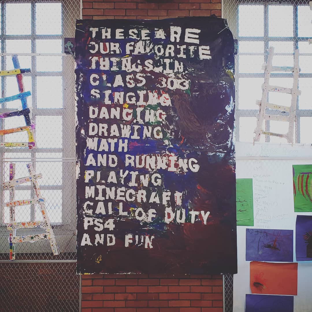 "The poem hanging up on a brick school wall. Other pieces of art from other projects surround it: individual drawings and crafted ladders. The paint colors (red, blue, brown, black, yellow, green) have dried. The poem reads ""These are / our favorite / things in / class 303 / Singing / Dancing / Drawing / Math / And running / playing Minecraft / call of duty / PS4 / and Fun"""