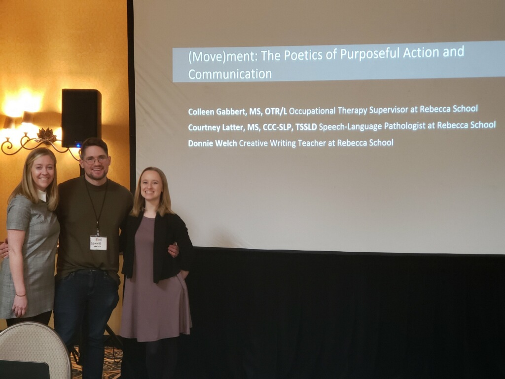 From left to right: Colleen Gabbert, young white woman. Donnie Welch young white man. Courtney Latter young white woman. All dressed professionally. The three are posing in front of their title slide on a large presentation screen with a black, curtain skirt. Behind them can be seen a speaker and light as well as the navy-yellow rug and yellow wall of the hotel ballroom.