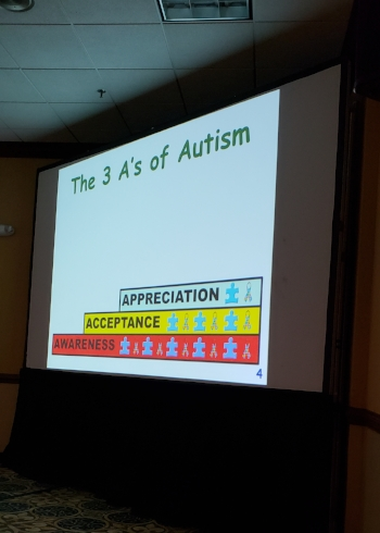 "Large presentation screen with a black curtain skirt on the bottom. On the top in Green is "" The 3 A's of Autism"" below is a stack of three words showing each concept as a foundation for the other. From the bottom up in red ""Awareness"" in yellow ""Acceptance"" and in light blue ""Appreciation"":"
