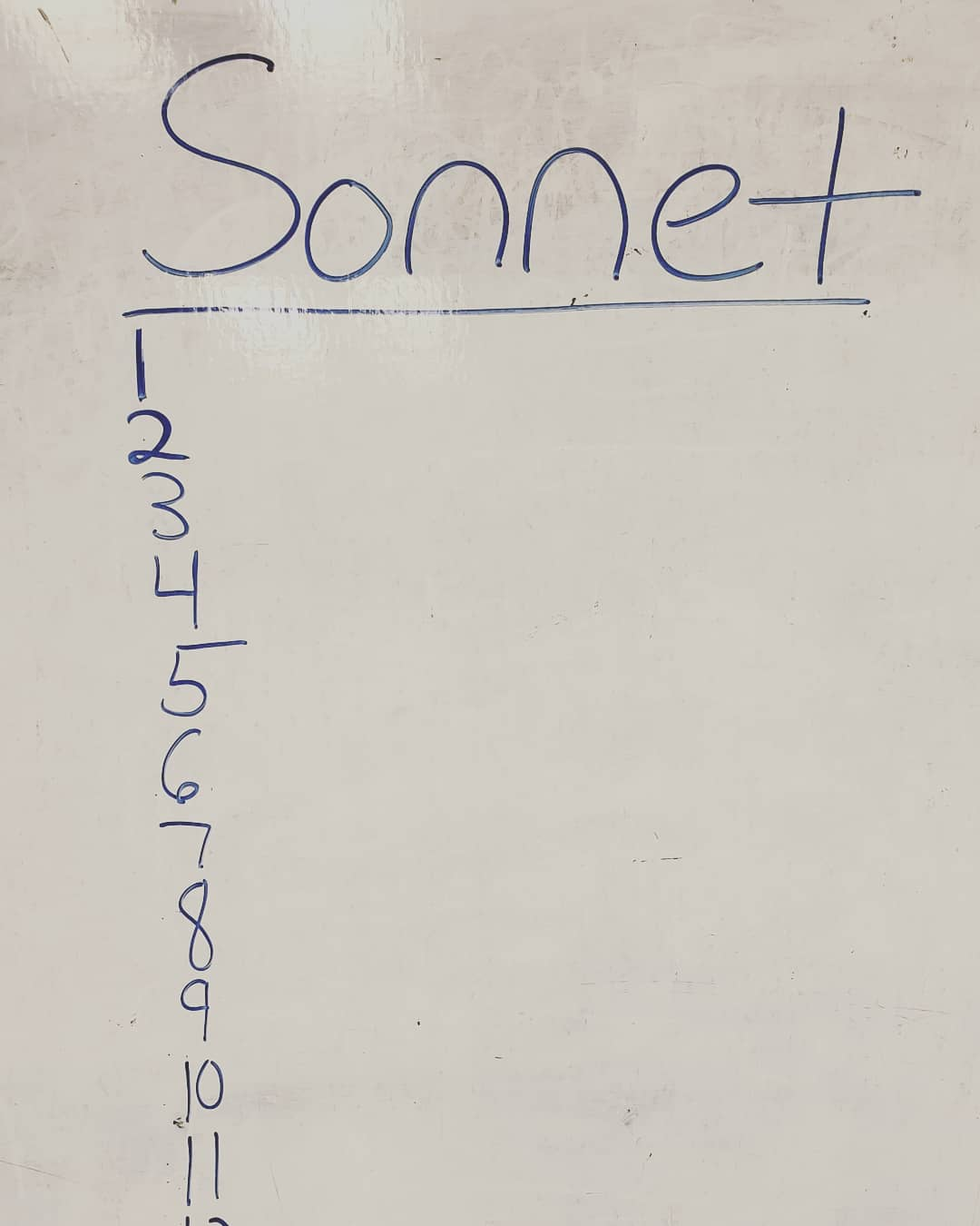 on a white dry erase school board the word Sonnet is written at the top with a vertical stack of numbers 1-14 underneath it. All the writing is in blue.