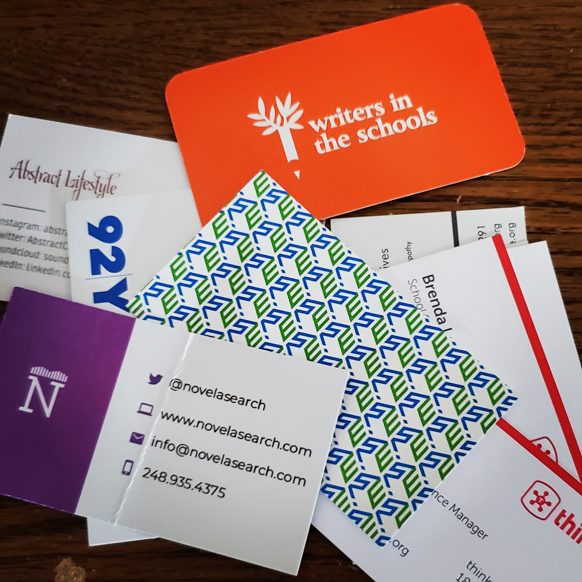 Pile of business cards, mostly white with colored text and images, on top of a brown wooden desk.