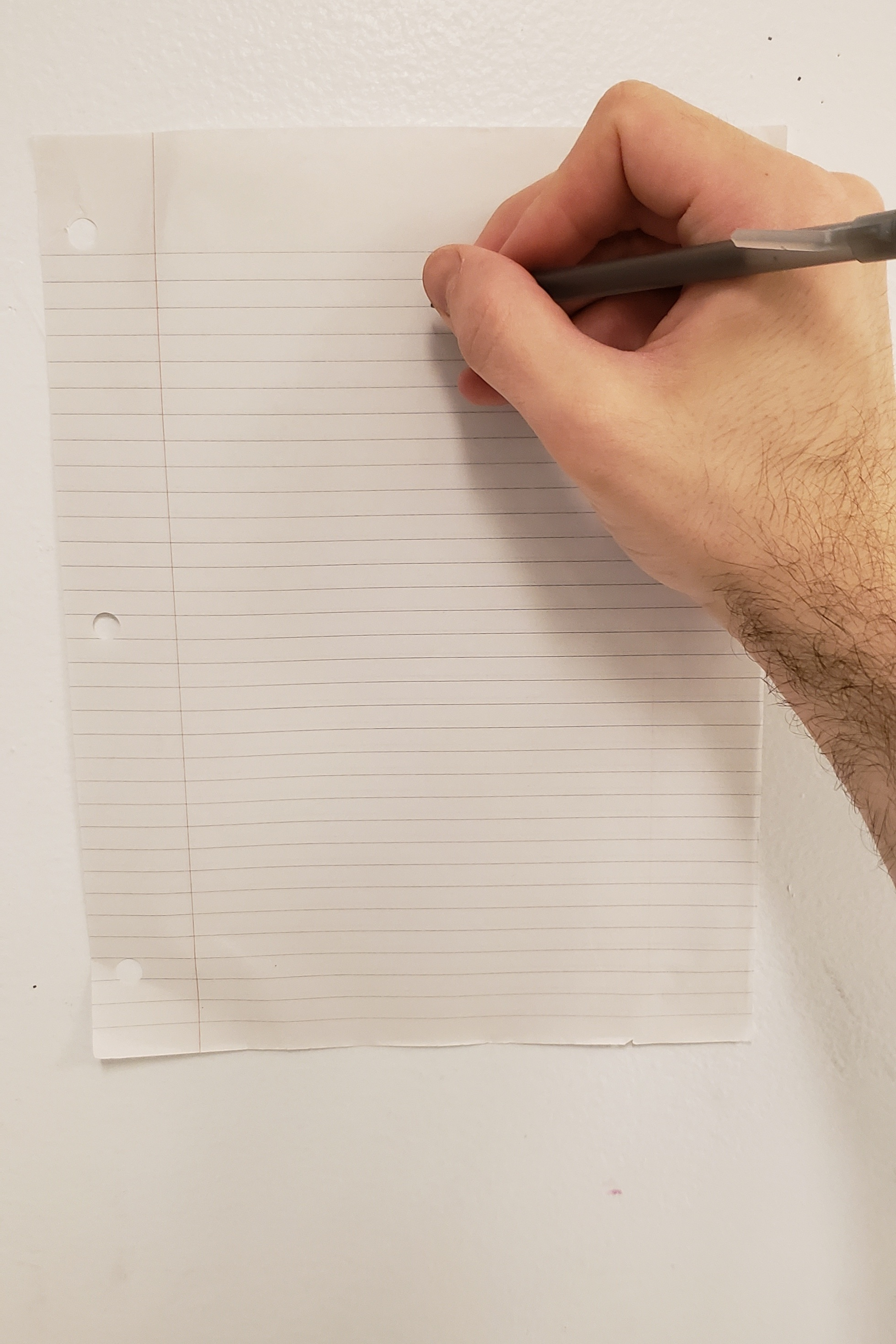 A hand holds a pen to a piece of lined paper taped to a white school wall.