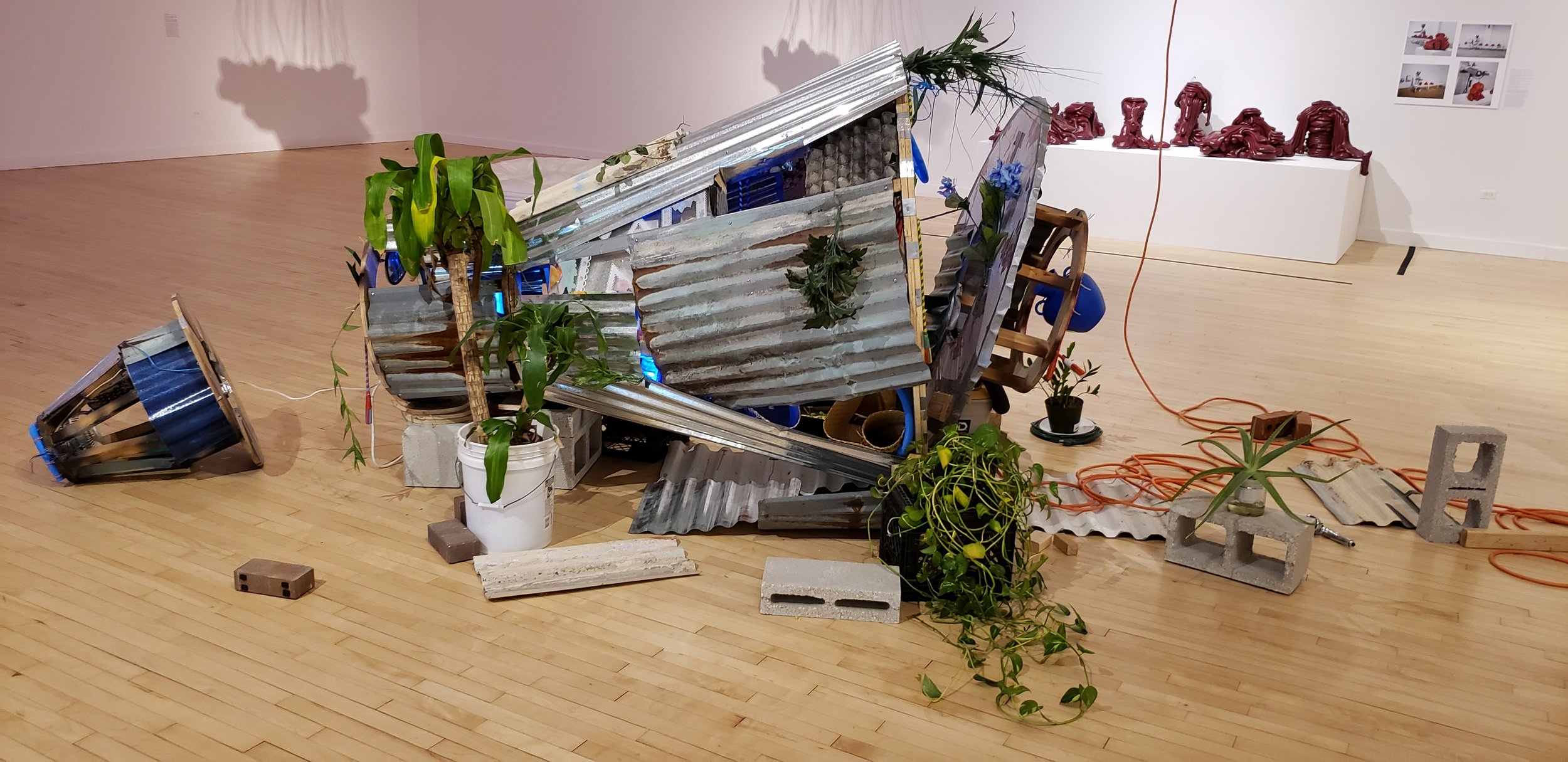 Contemporary art installation on a hardwood floor. The art work looks like a 1970's space capsule, but covered in sheet metal, plants, and bricks. Extension cables can be seen running out of the piece as well. In the background are other photos and statues.