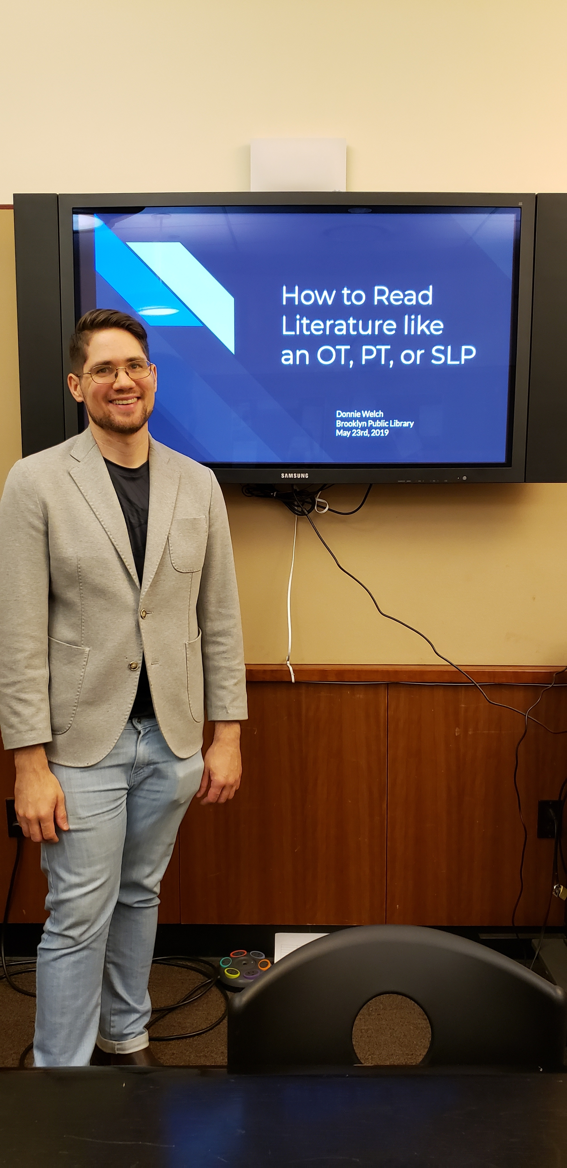 "Donnie Welch, a young white man, stands smiling at the front of a room in business casual attire. Behind him on a large, computer monitor is a presentation title slide reading, ""How to Read Literature like an OT, PT, or SLP"" in white lettering on a blue background."