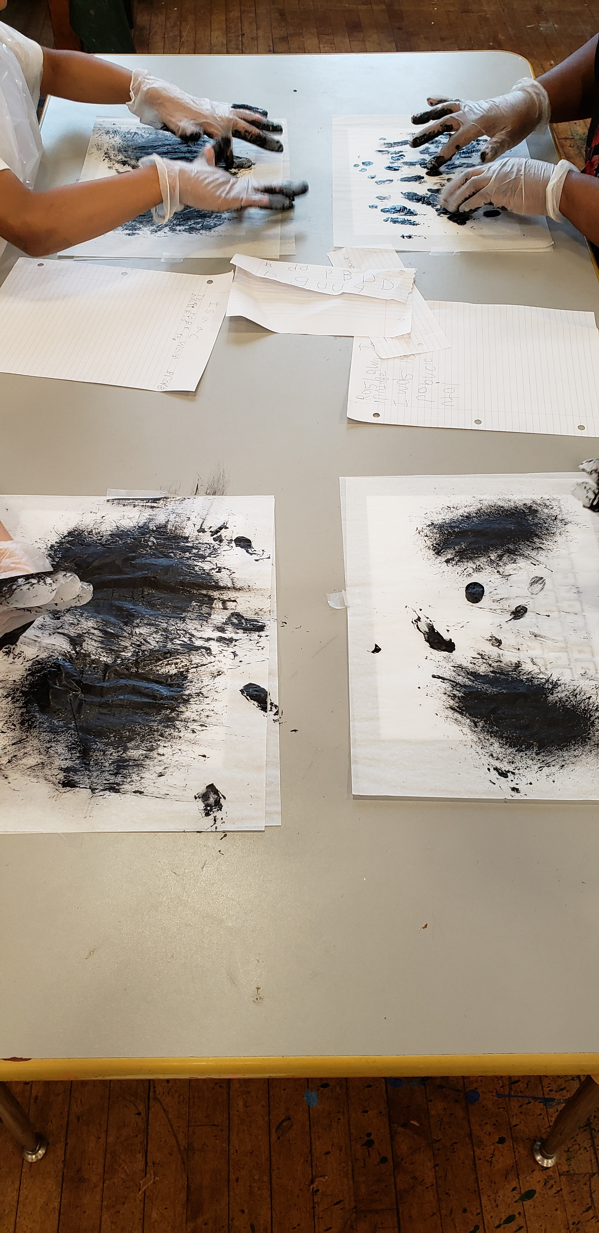 "On the art room tables students hands can be seen covered in gloves and black paint ""typing"" on the tracing paper."