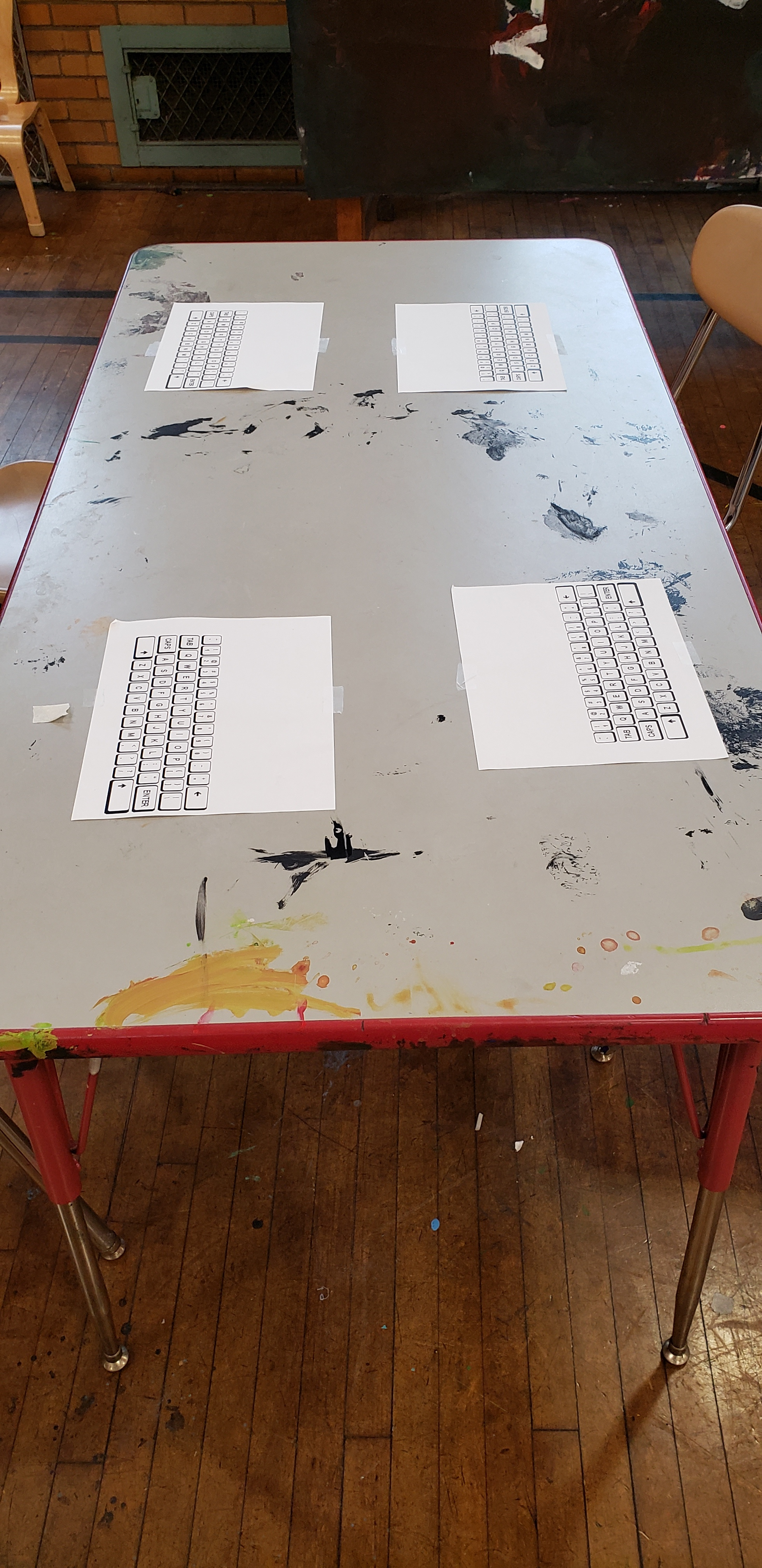 On an art room table, covered in old paint marks, print outs of computer keyboards are taped down.