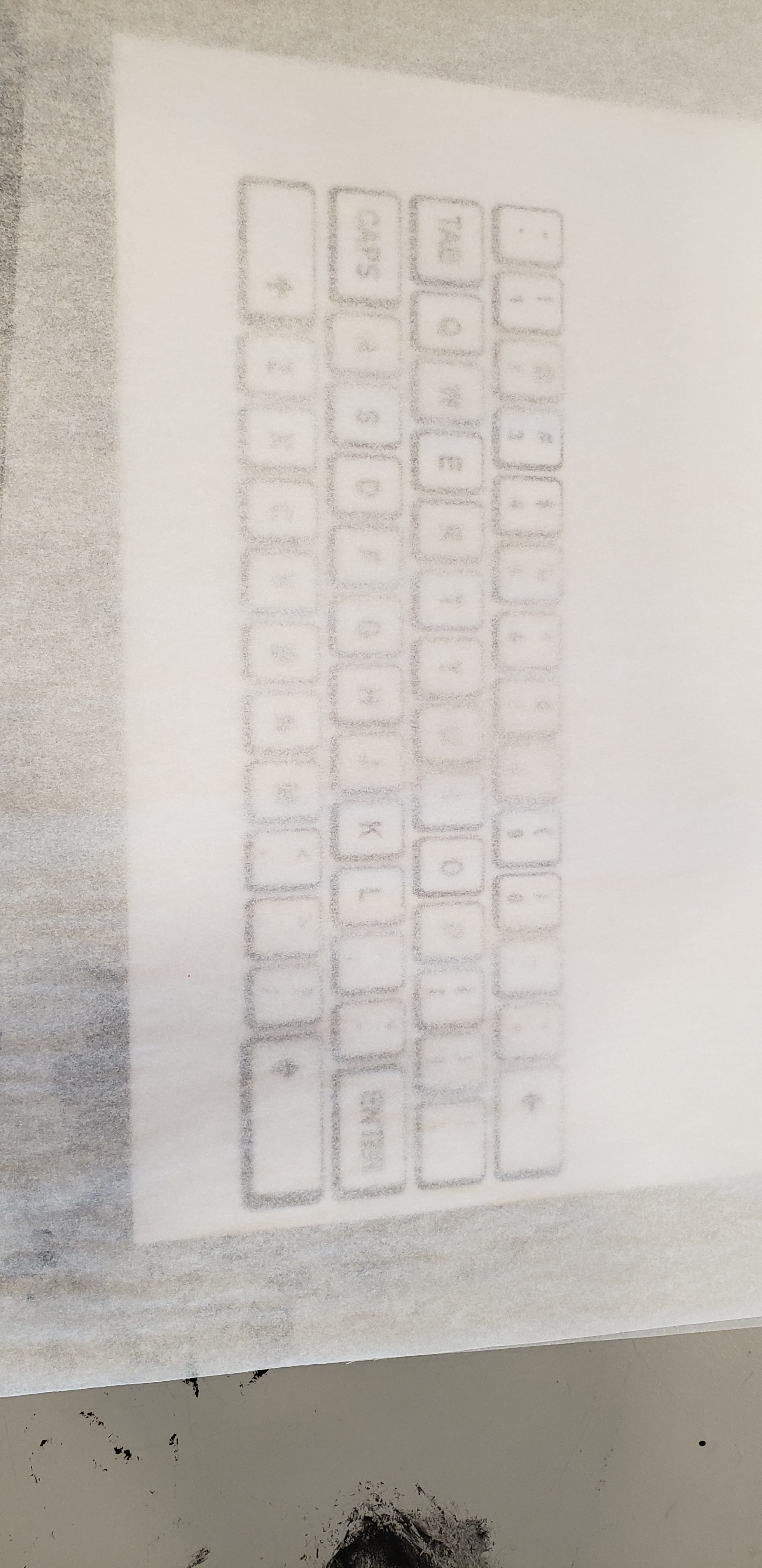 Close up of the art room table, the keyboard print outs are now covered by a piece of tracing paper so that the keys themselves are still visible.