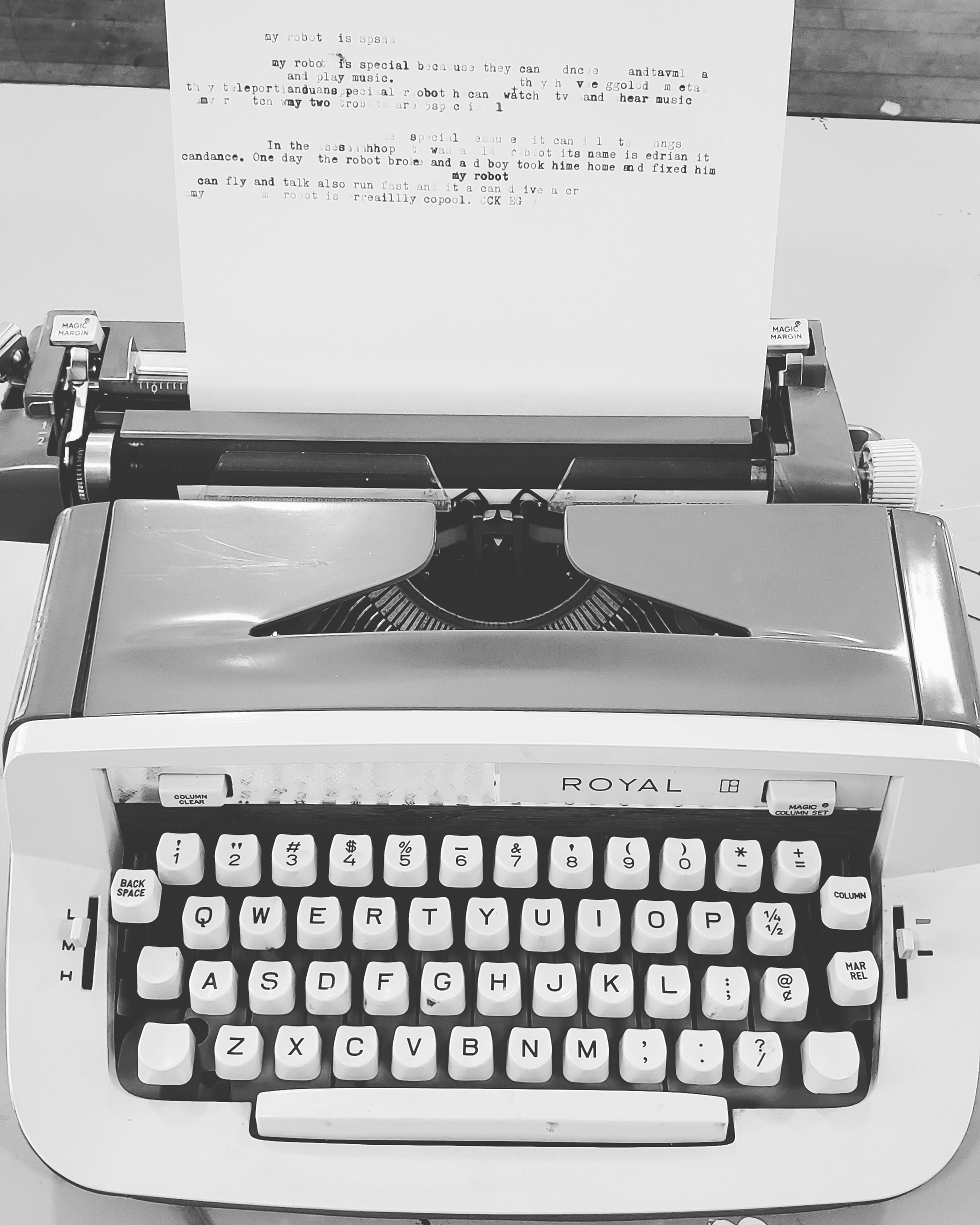 Black and White photo of a 1970s typewriter. A paper with some typing is loaded into the scroll.