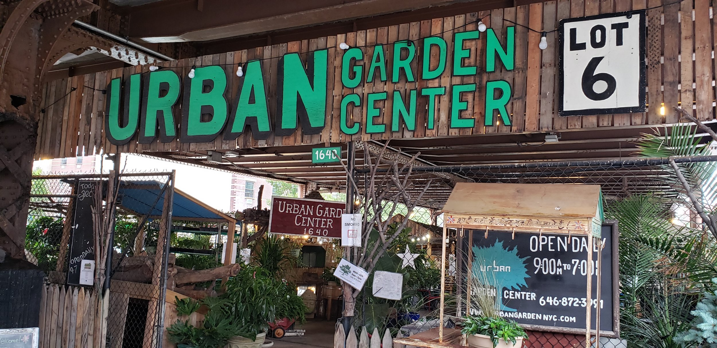 "Entrance to the store ""Urban Garden Center"" The store's name is in large green block letters on a wooden frame with the word ""Urban"" being the largest. In the background can be seen plants and garden supplies such as fencing as well as signs denoting the stores hours and sales."