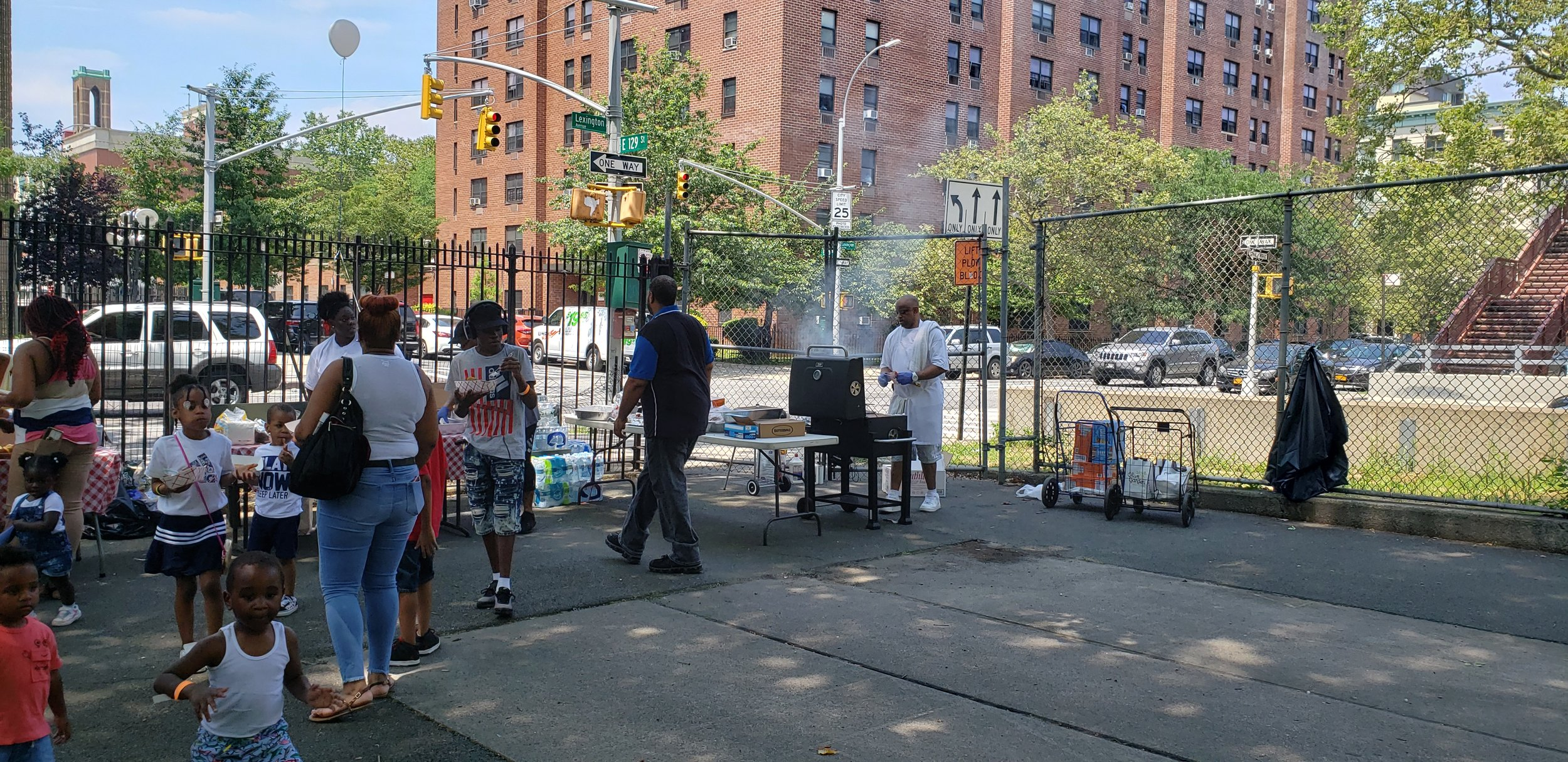 Autism Family Fun day grill set up, families and children are in the foreground of a shot of a food line. Tables in the background have the food on them and in the top right of the photo the grill master cooks while smoke can be seen coming off the grill.