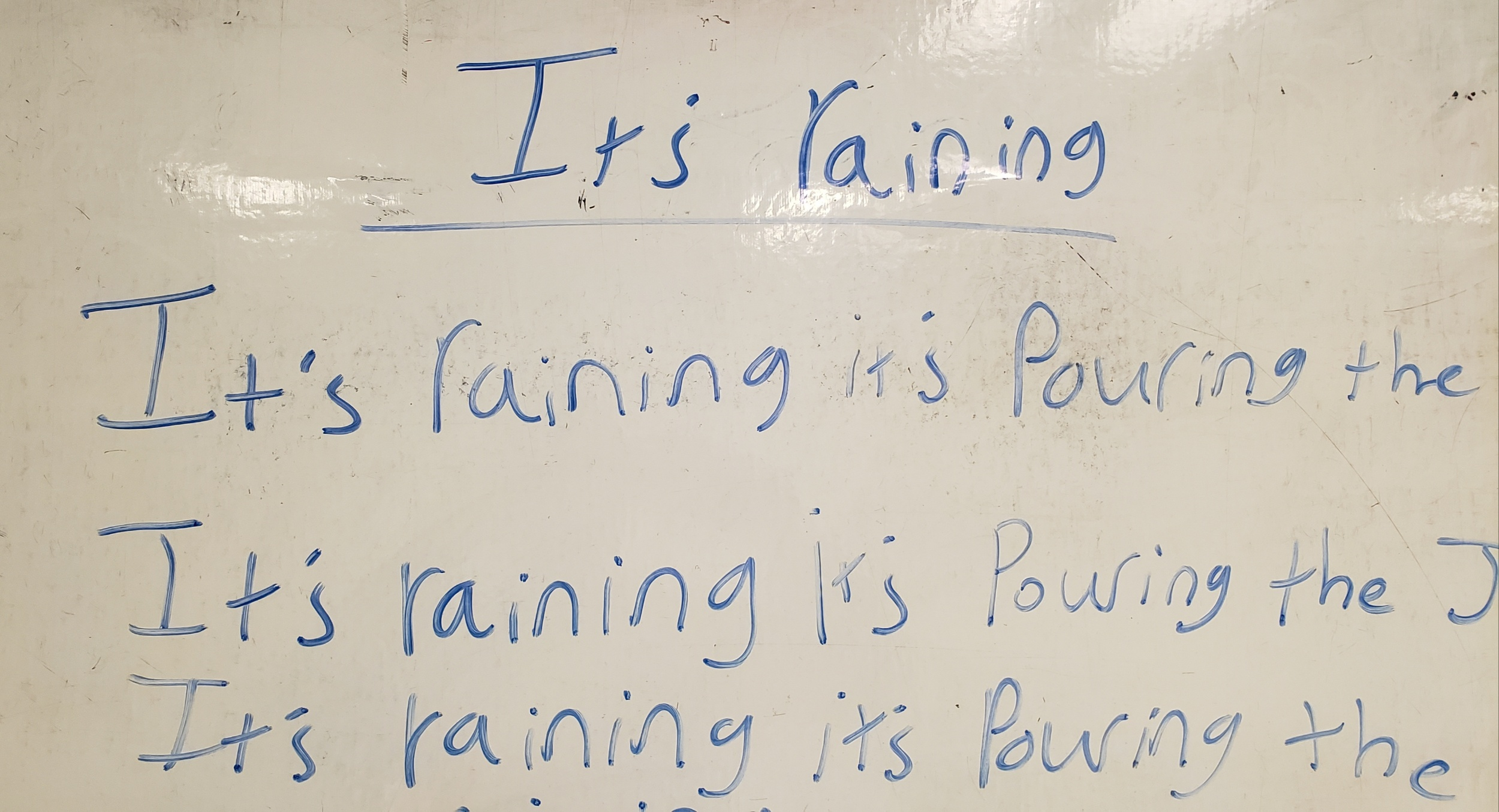 "Words on a white board in blue expo marker read ""It's raining it's pouring the"" This line is repeated again and again."