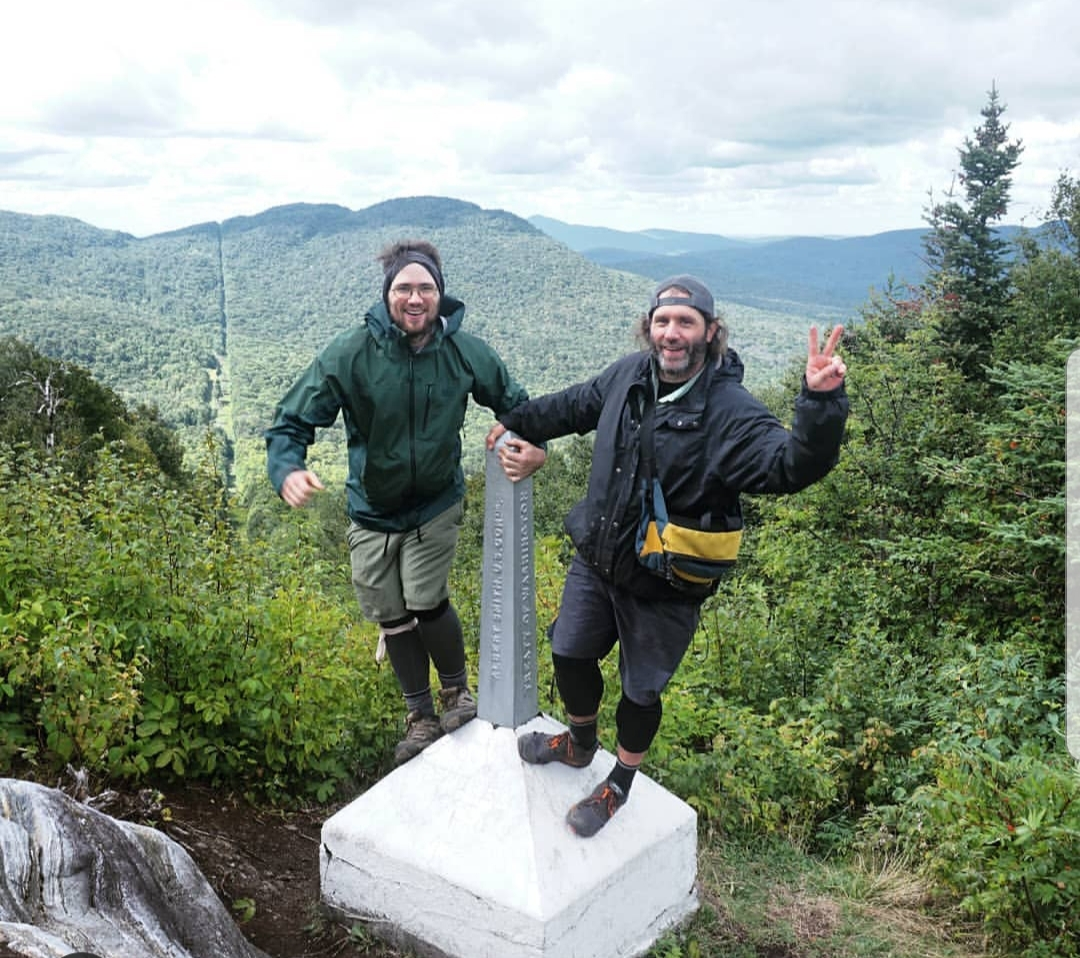 Donnie Welch and Jonathan Welch, two bearded young men, stand on the Canadian-US border in Vermont. The two are standing on a silver, spiked monument with a white base which denotes the border line. Behind them can be seen mountains and forests with a clear cut line for the border. The looks on their faces are ones of excitement and joy