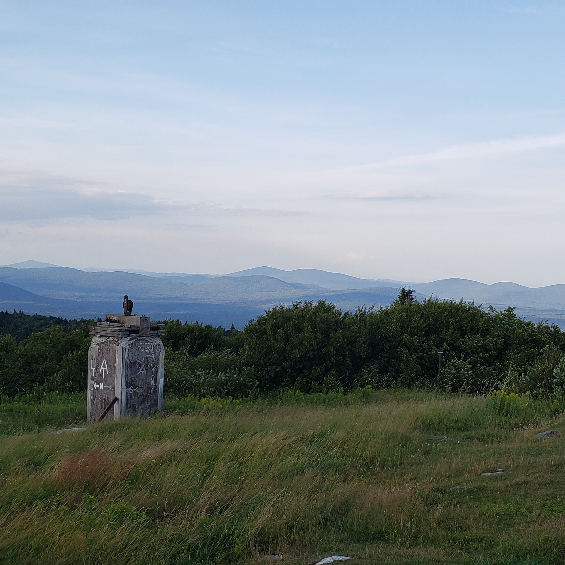 Sunset view off Bromley Mountain. In the foreground is a field of tall grass bent by the wind and an old stone work with LT and AT symbols and white N for North painted on in white.In the background can be seen ranges of mountains pale blue and purple from the light at sunset.
