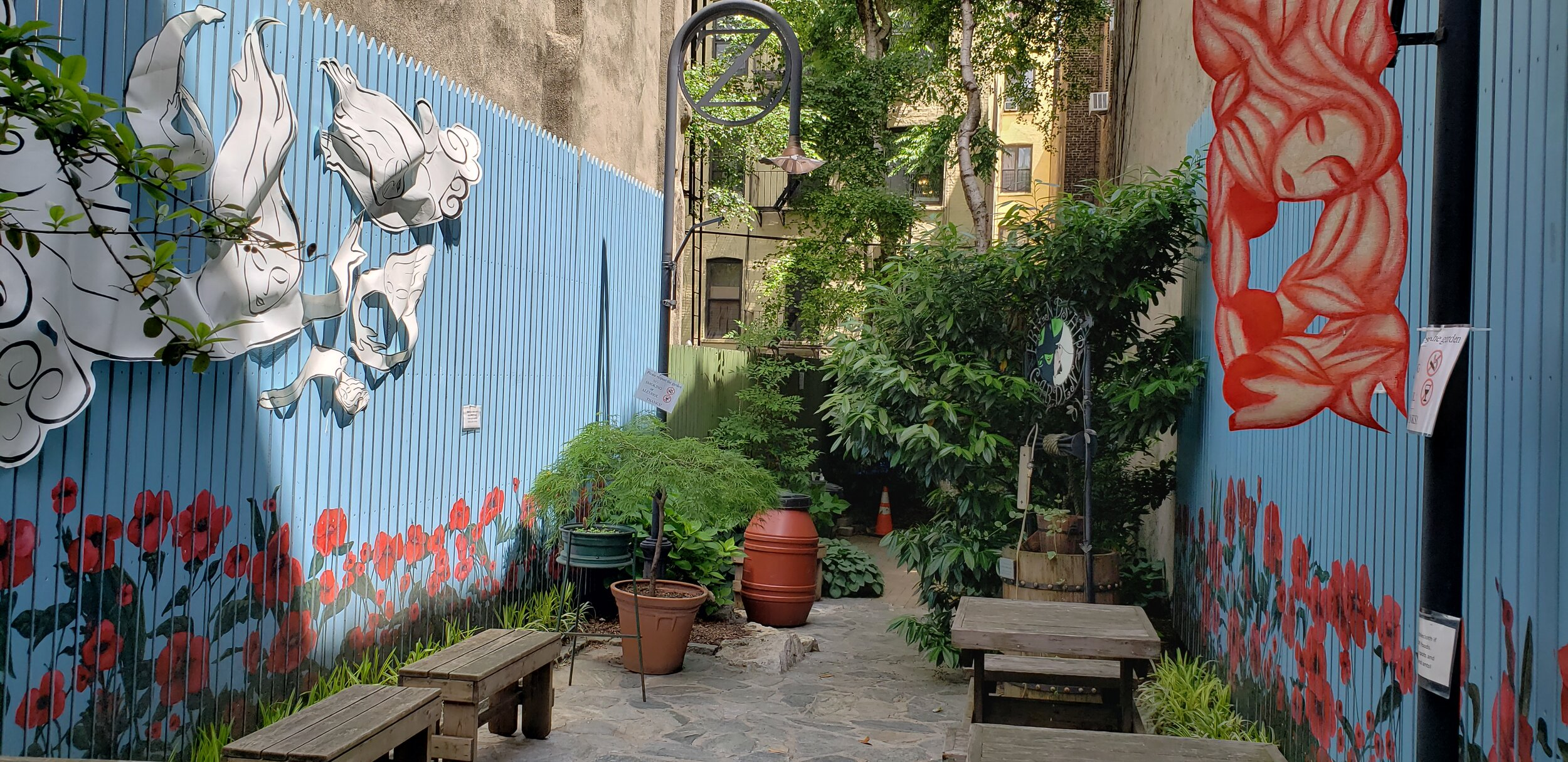 Community garden tucked between tall New York City buildings. In the foreground can be seen pavers marking a path, benches, compost bin, rain bucket, and array of trees and bushes. The side fencing of the garden is painted teal with red, poppy flowers painted eye level. Above are hung red and white cloud-human figures from a recent public-art exhibit.