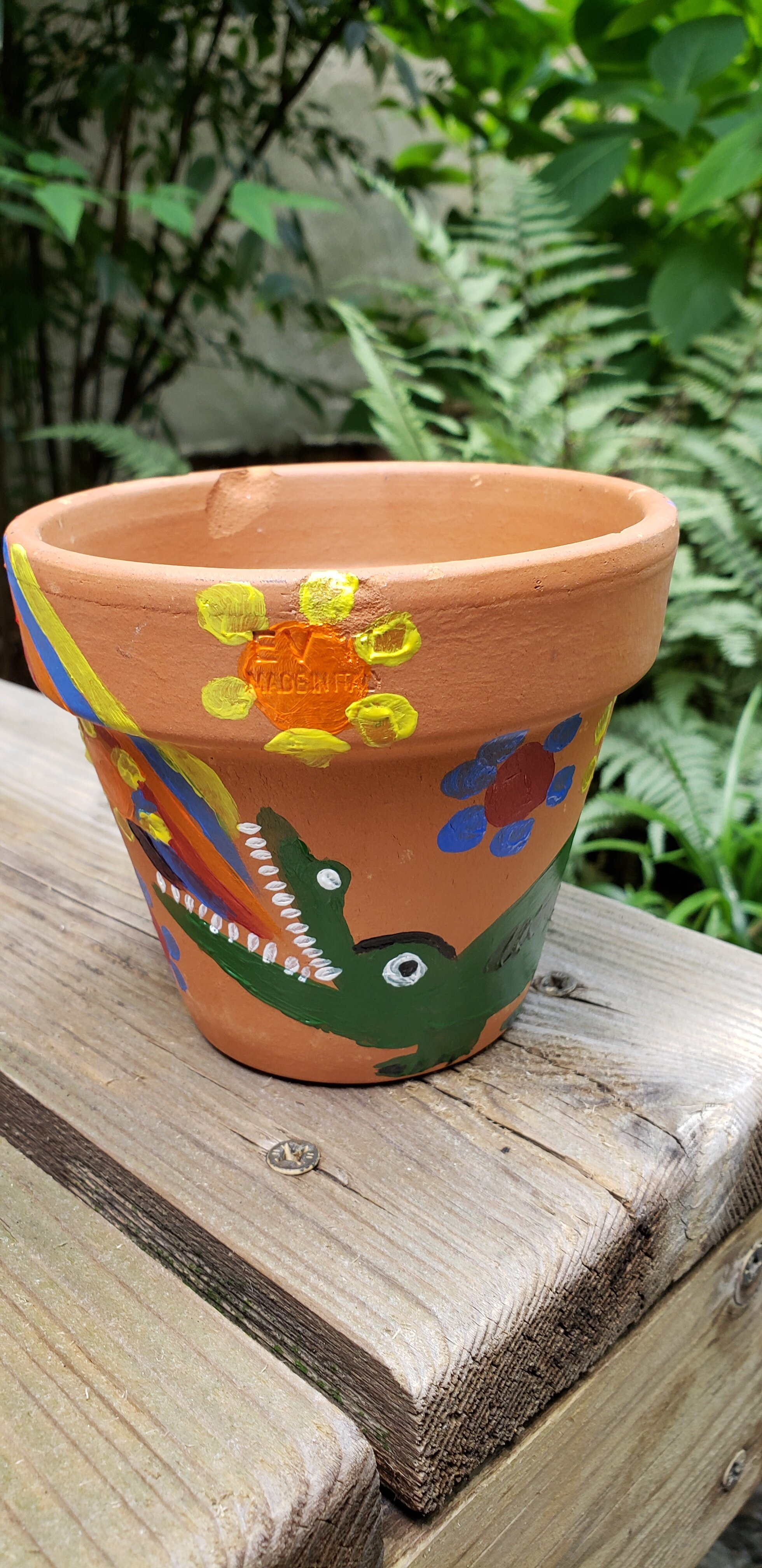Terra Cotta flower pot with a painted green alligator. The alligator has a rainbow coming out of its mouth and flowers around it. The pot is sitting on a wooden bench and in the background is the greenery from a bush and ferns.