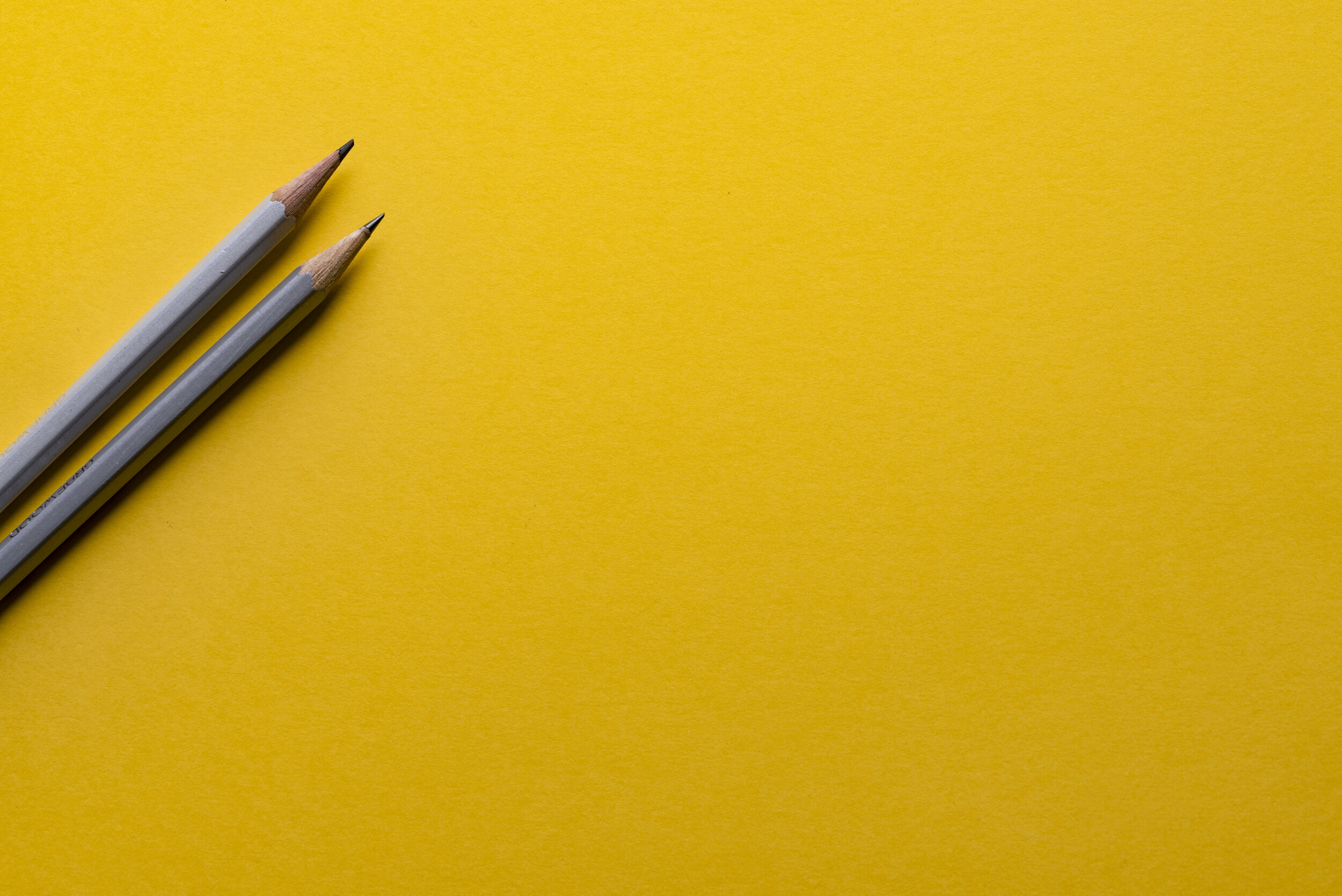 Two gray pencils lie side-by-side  on the far most side of yellow table top