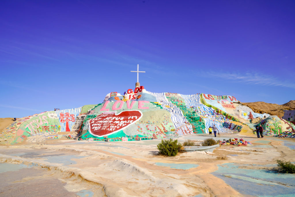 "Salvation Mountain, with the Sinner's Prayer enclosed in a bright red heart, perched above the boats and blue waves of the ""Sea of Galilee"""