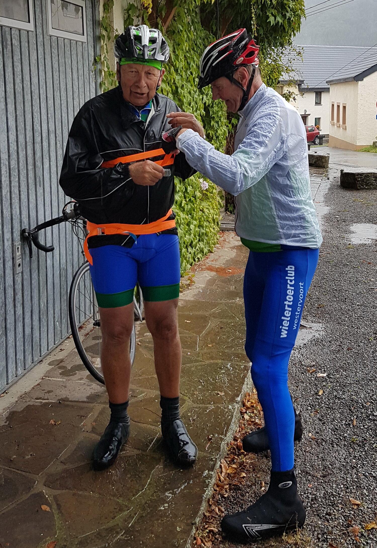 Theo zijn regenjas gaat niet meer dicht. Paul gebruikt een spanband om hem dicht te krijgen. Theo gaat verder als fietstende rollade. Had ik al gezegd dat het nat was?