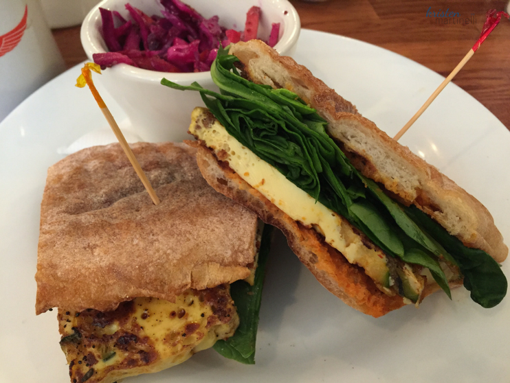 Description: Mexican chorizo or Zucchini & egg white frittata with summer squash and potato on ciabatta. Topped with harissa and fresh spinach. Served w/ choice of cabbage-apple slaw or side salad