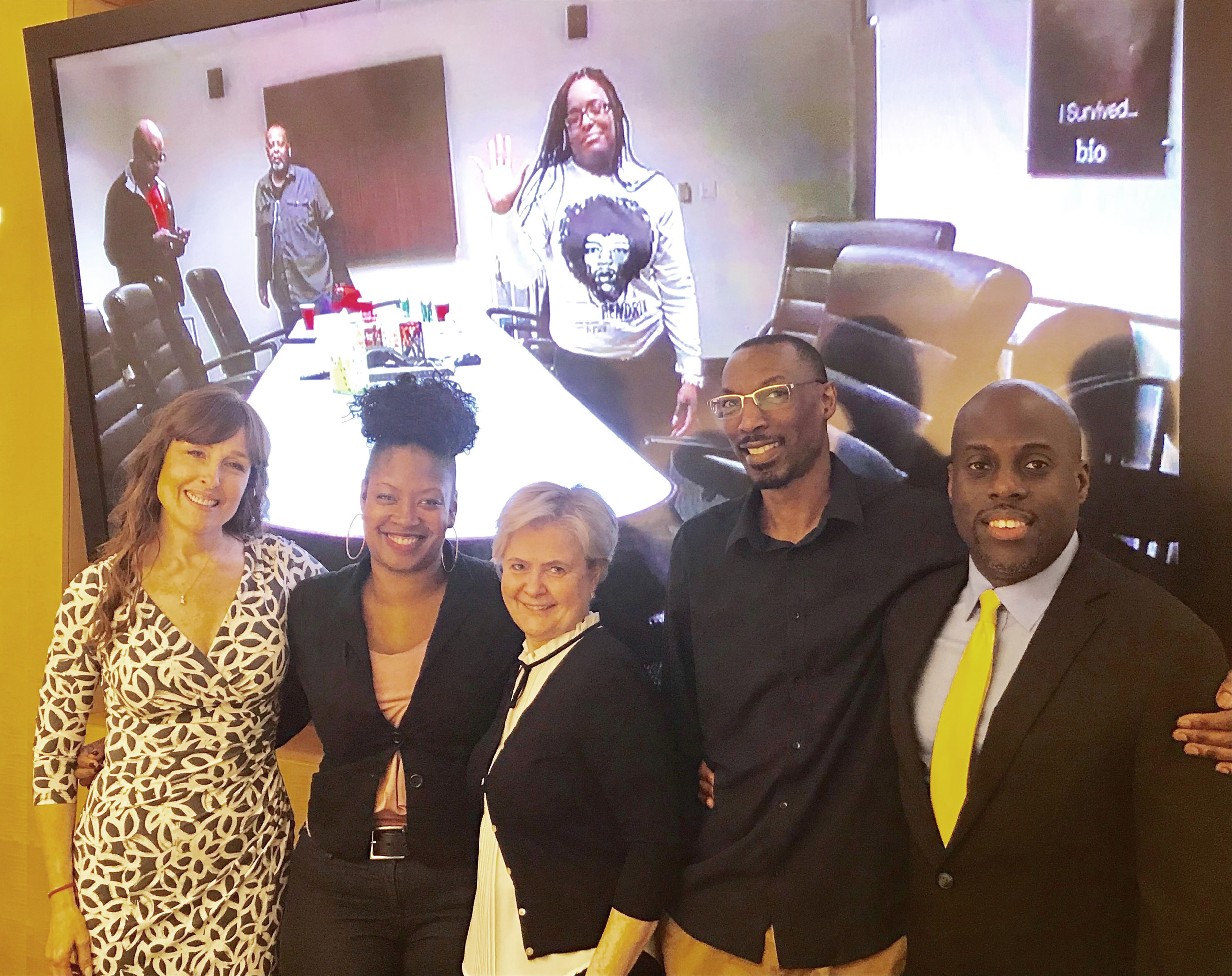 Photo L-R: Denise Strong - client, Jasmine Taylor, Elwira Cabala, Stephanie Williams (standing on video monitor), Godfrey Smallwood, Omar Roberts