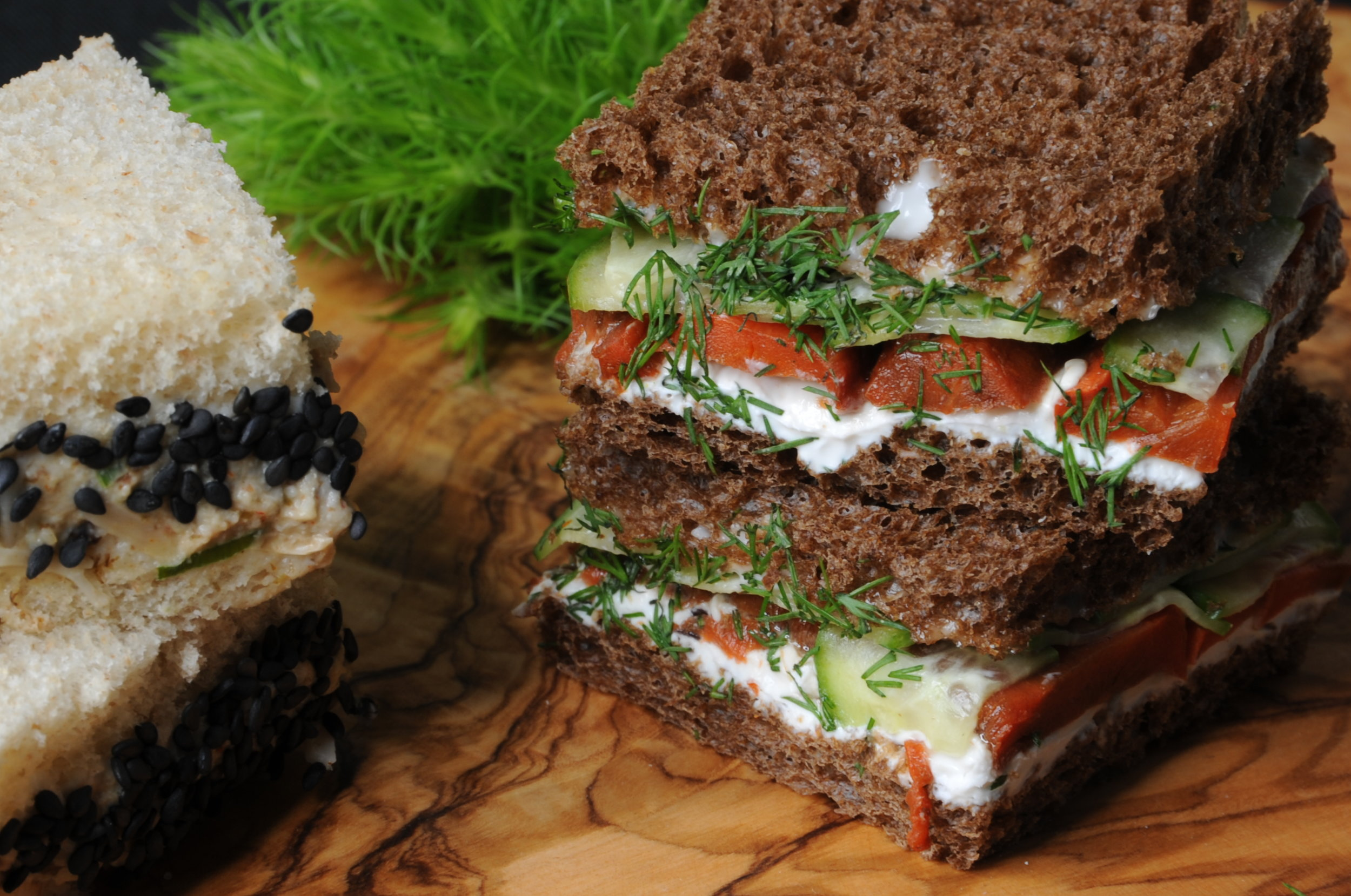 A selection of tea sandwiches including a jackfruit tuna with black sesame seeds and cucumber tomato with dill aioli