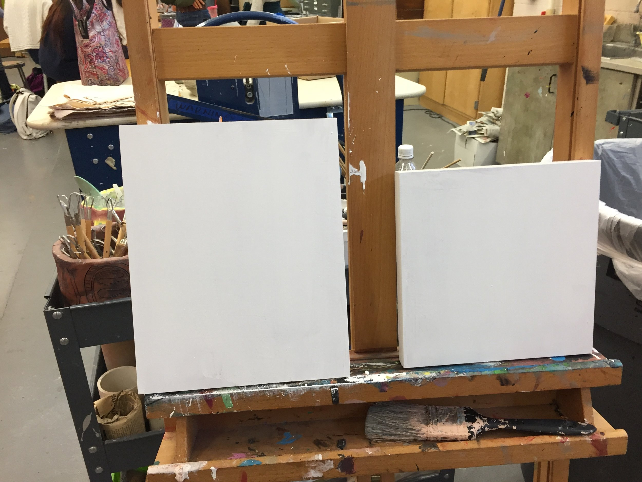 Working on painting a base layer on the wooden canvas.