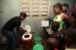 SOIL  Volunteers show a Haitian family how to use their new EcoSan composting toilet. This simple technology is life-changing for families that have been going without.  Photo courtesy of    SOIL   .