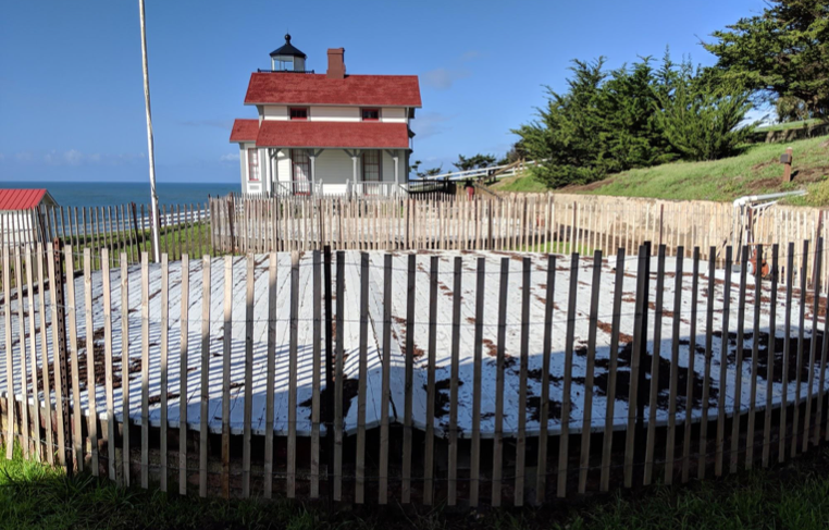 The two cisterns surrounded by safety fence with the lighthouse in the background.