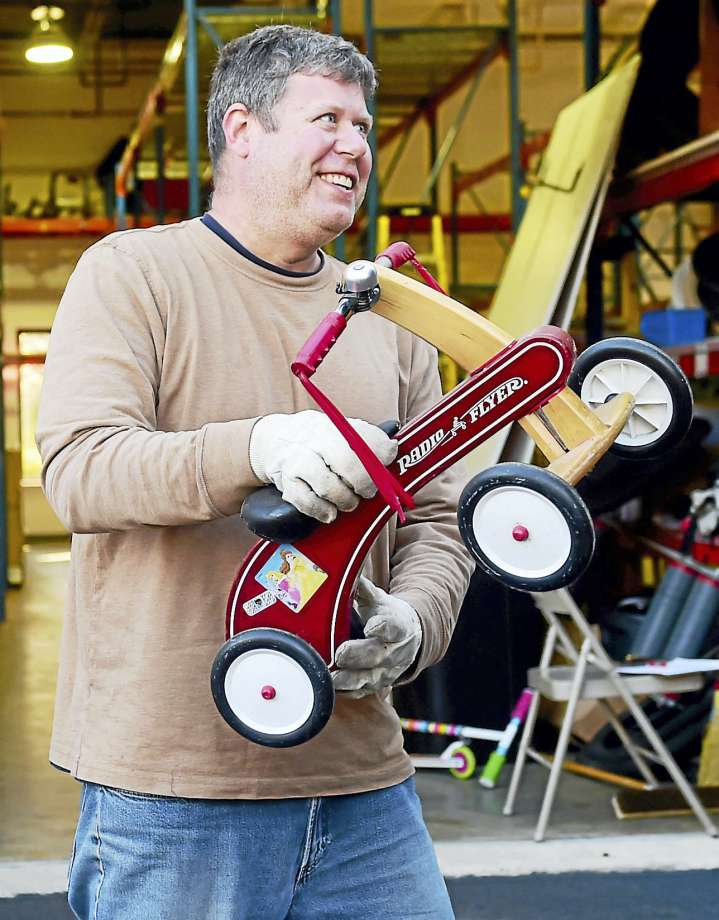 Volunteer Brian Lewis of Old Saybrook, left, helps Bikes For Kids move by loading a tricycle onto a Zanes Cycles delivery truck from the former Old Saybrook location. (Photo by Peter Hvizdak — New Haven Register)